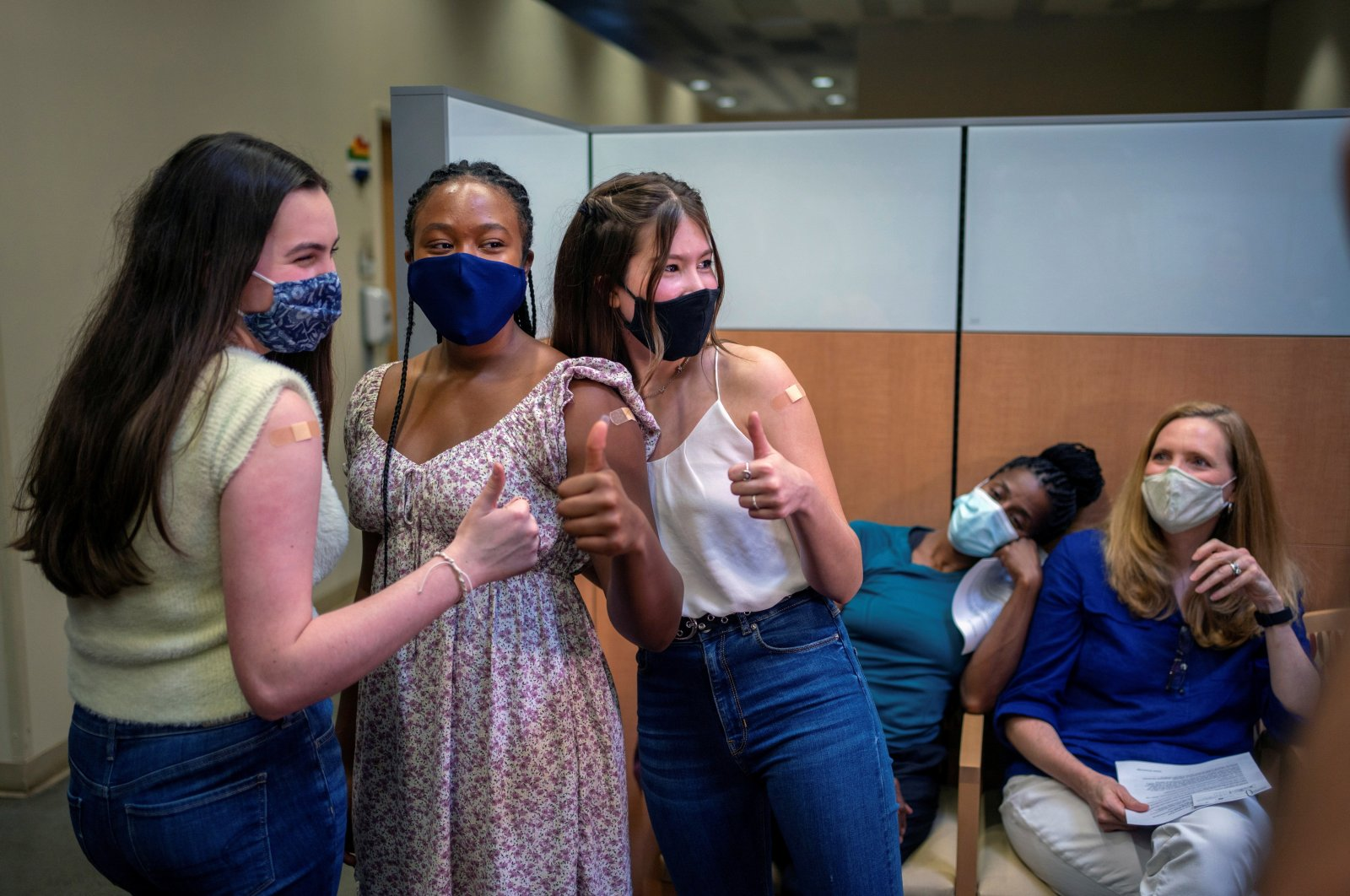 Lilly Gorman, 15 (L) Croix Hill, 15 and Ava Kreutziger, 14, give a thumbs up after the Isidore Newman School students received their first dose of the COVID-19 vaccine at the Ochsner Center for Primary Care and Wellness, New Orleans, Louisiana, U.S., May 13, 2021. (Reuters File Photo)