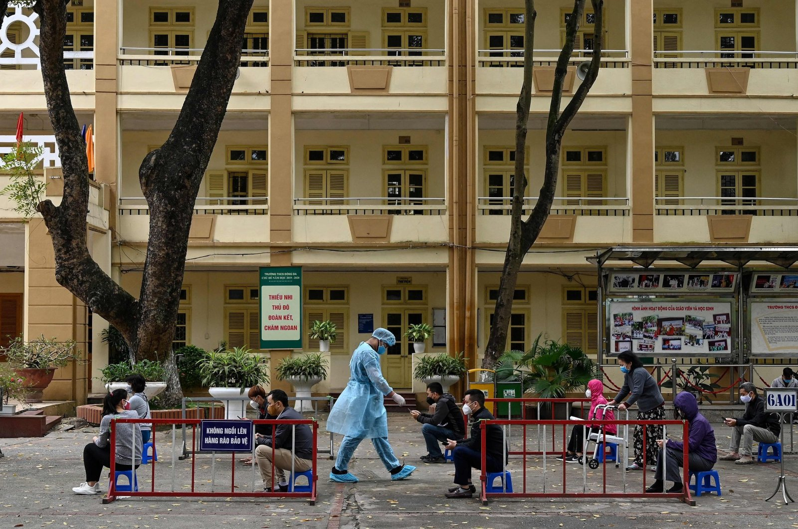 Residents, wearing face masks as a preventive measure against the spread of the COVID-19, practice social distancing as they wait to be tested at a makeshift rapid testing center near the Bach Mai hospital in Hanoi, Vietnam, March 31, 2020. (AFP Photo)