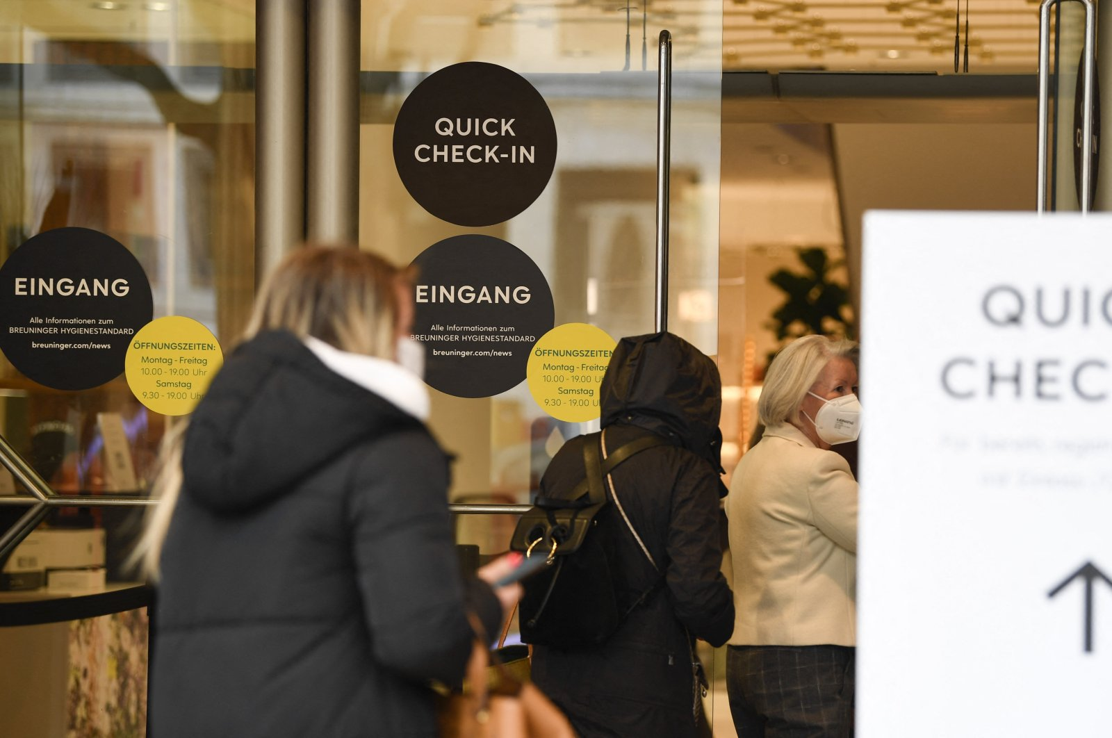 People line up in front of the entrance of a fashion store in Stuttgart, southern Germany, May 26, 2021. (AFP Photo)
