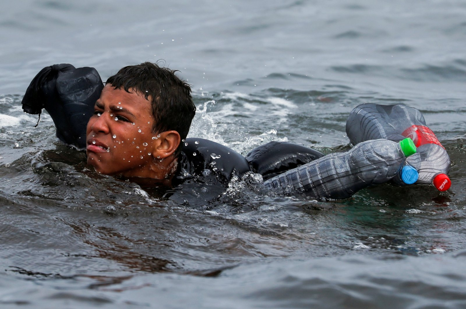 A Moroccan boy swims using bottles as a float, near the fence between the Spanish-Moroccan border, after thousands of migrants swam across the border, in Ceuta, Spain, May 19, 2021. (Reuters Photo)