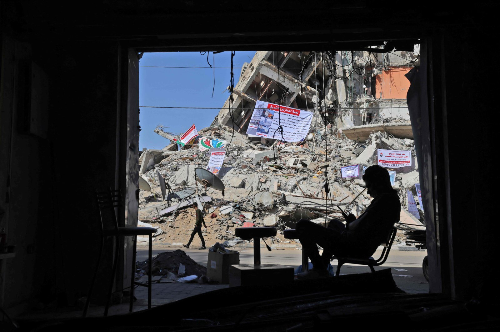 A man sits in a damaged shop at a building partially destroyed in recent Israeli air strikes, in Gaza City, Palestine, May 26, 2021. (AFP Photo)