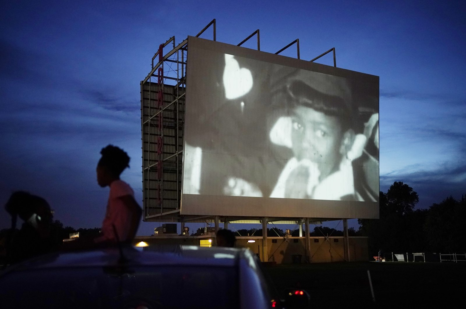 """People watch the documentary """"Rebuilding Black Wall Street,"""" during a drive-in screening of documentaries during centennial commemorations of the Tulsa Race Massacre in Tulsa, Okla, May 26, 2021. (AP Photo)"""