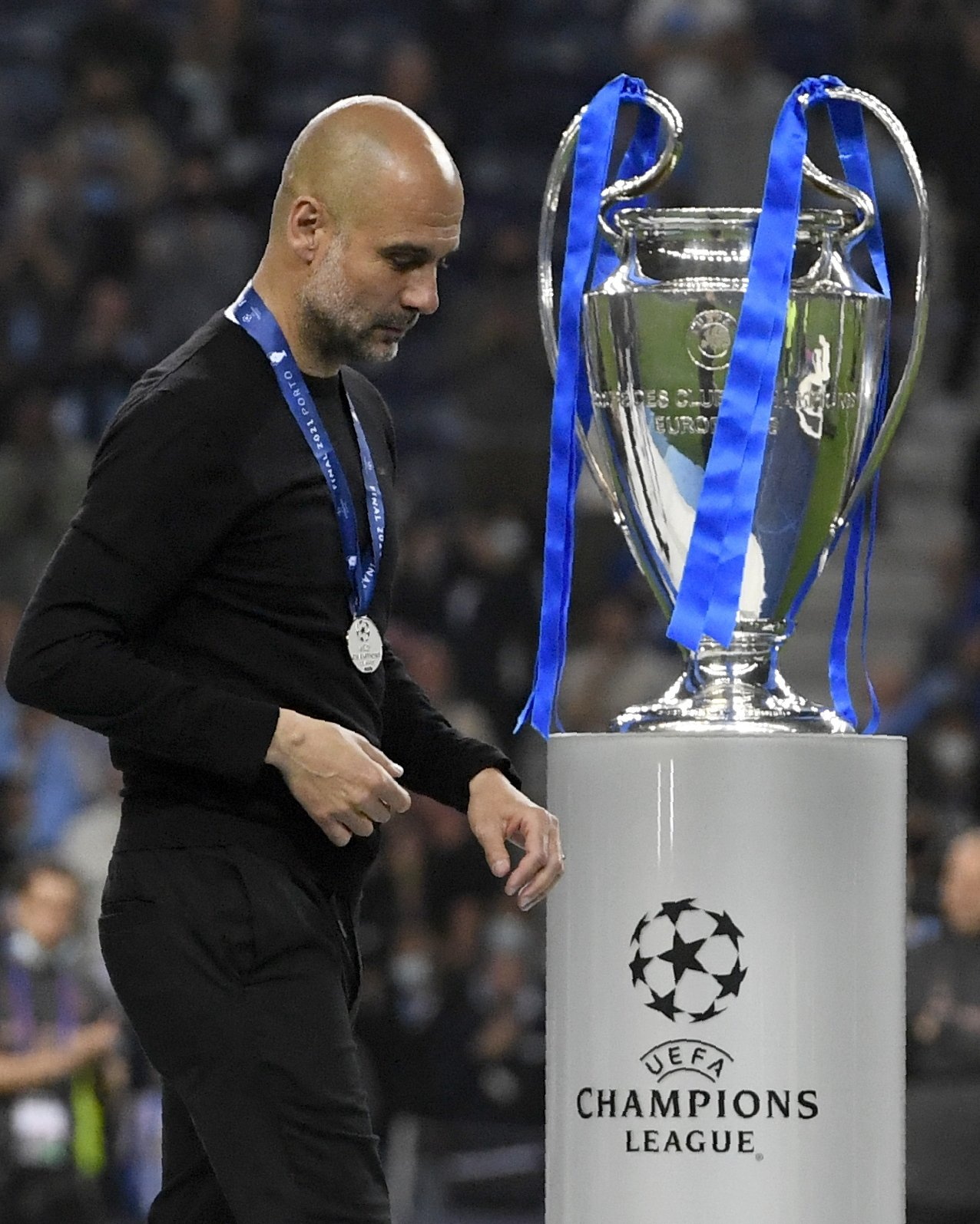 Manchester City's head coach Pep Guardiola walks past the trophy after the Champions League final match against Manchester City at Dragao Stadium in Porto, Portugal, May 29, 2021. (AP Photo)