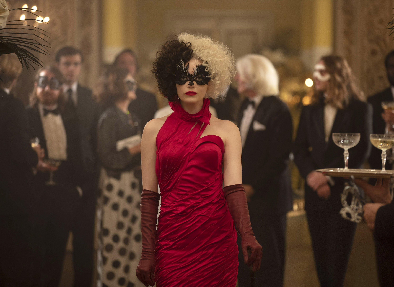 Emma Stone (C) wearing a face mask and a striking red dress walks amid a crowd in a scene from Disney's 'Cruella.' (Disney via AP)