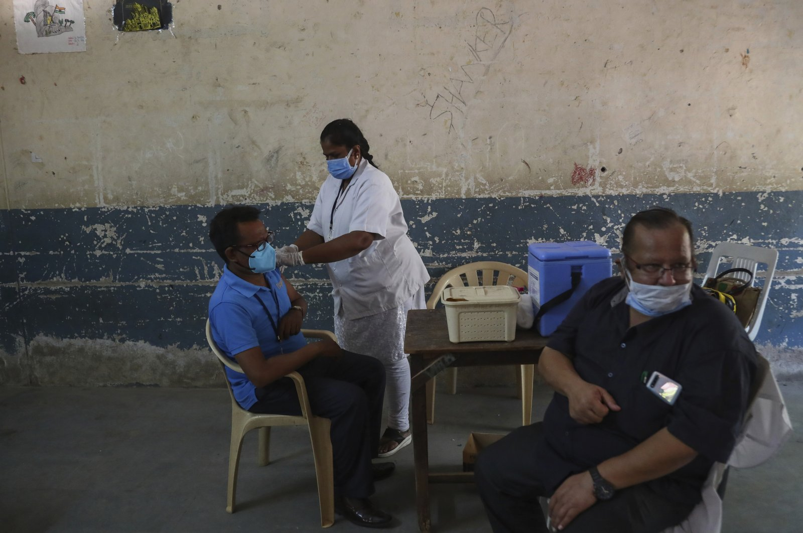A health worker administers Covishield, the Serum Institute of India's version of the AstraZeneca vaccine, to a man during a special vaccination drive held on the premises of a government school in Hyderabad, India, May 30, 2021. (AP Photo)