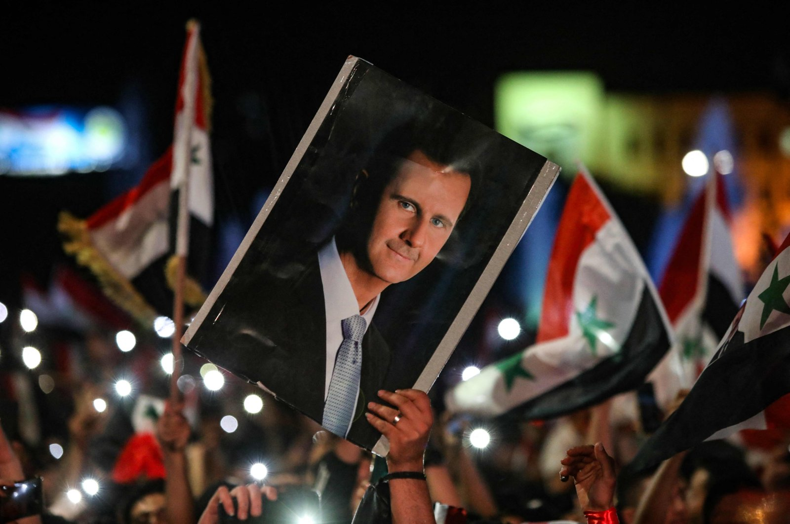 Syrians wave national flags and carry a portrait of Bashar Assad as they celebrate the result of the presidential election, Damascus, Syria, May 27, 2021. (AFP Photo)