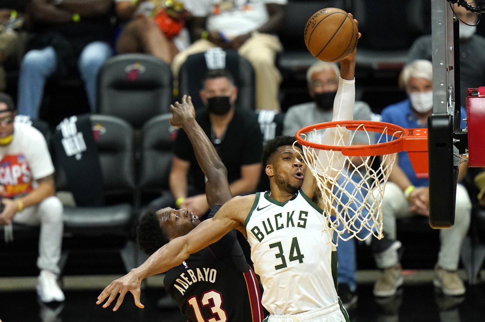 Milwaukee Bucks forward Giannis Antetokounmpo (R) shoots as Miami Heat center Bam Adebayo (L) defends during the Game 4 of NBA first-round playoff series, May 29, 2021, in Miami. (AP Photo)