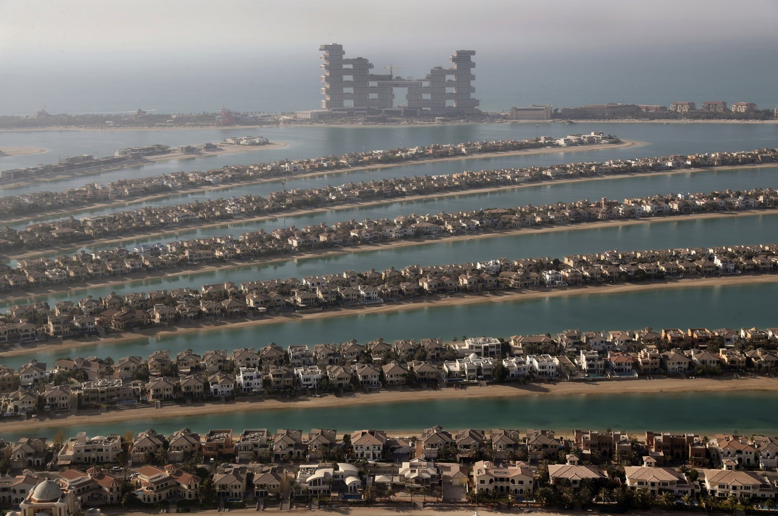 Villas on the fronds of Jumeirah Palm Island are seen from the observation deck of The View at The Palm Jumeirah, in Dubai, United Arab Emirates, April 6, 2021. (AP Photo)