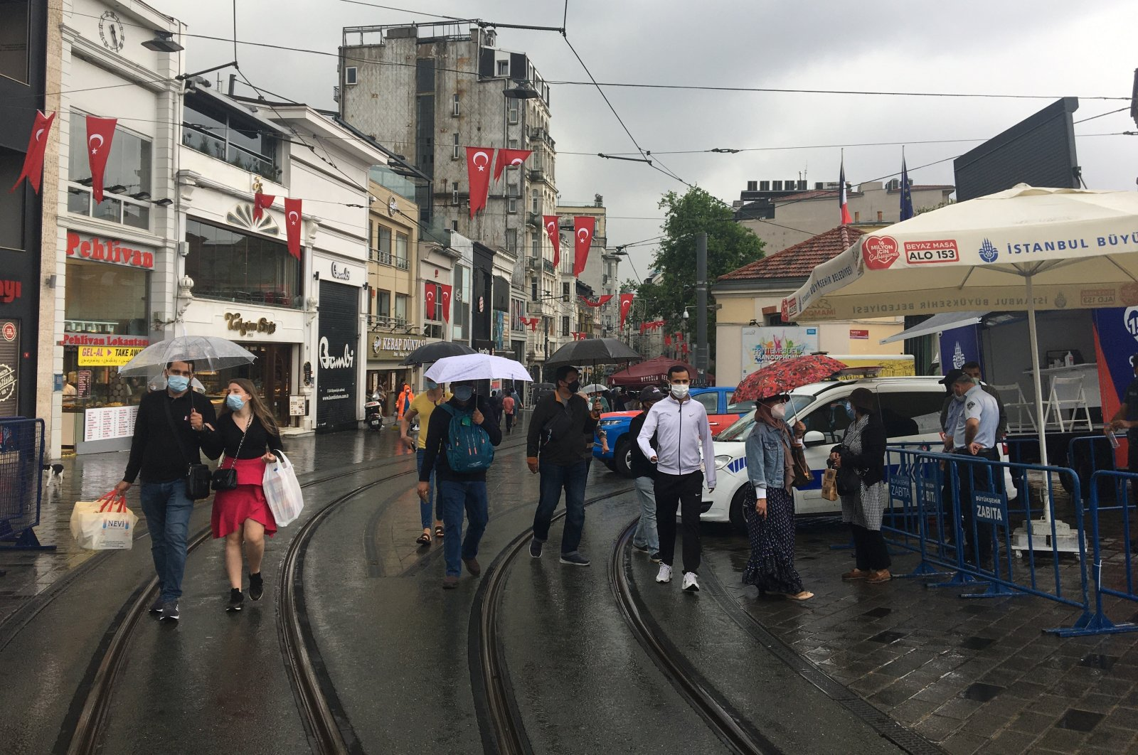 People wearing masks walk amid rainy weather at the entrance of Istiklal Avenue at the famous Taksim Square in Istanbul, Turkey, May 29, 2021. (IHA Photo)