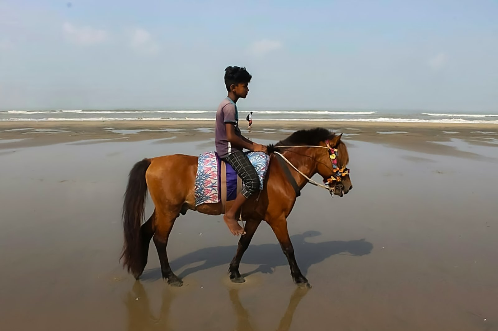 A youth waits for customers to ride on his horse, after some 21 horses have starved to death in the last month as COVID-19 lockdowns brought the country's most visited tourist spot to its knees, at a beach in Cox's Bazar, Bangladesh, May 29, 2021. (AFP Photo)