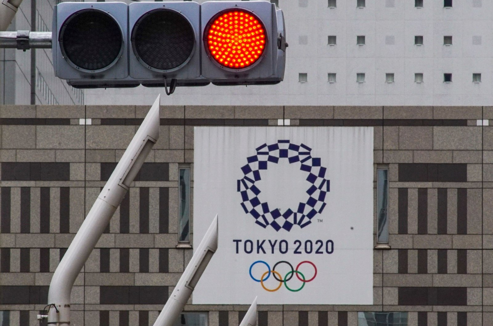 A red traffic light lights up on a street near the Tokyo Metropolitan Government Building displaying a banner of the Tokyo 2020 Olympics Games in Tokyo on May 31, 2021.(AFP Photo)