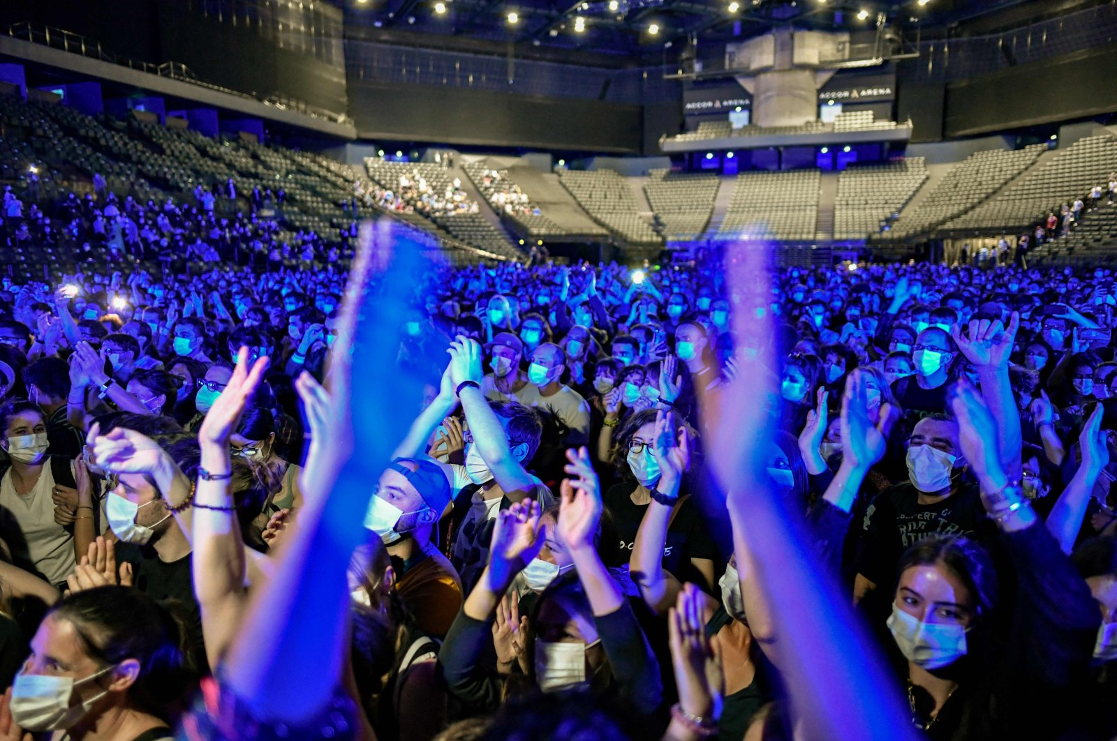 People cheer during a concert of French DJ Etienne de Crecy and rock band Indochine, aimed at assessing the risk of COVID-19 transmission at live events, at the AccorHotels Arena in Paris, France, May 29, 2021. (AFP Photo)
