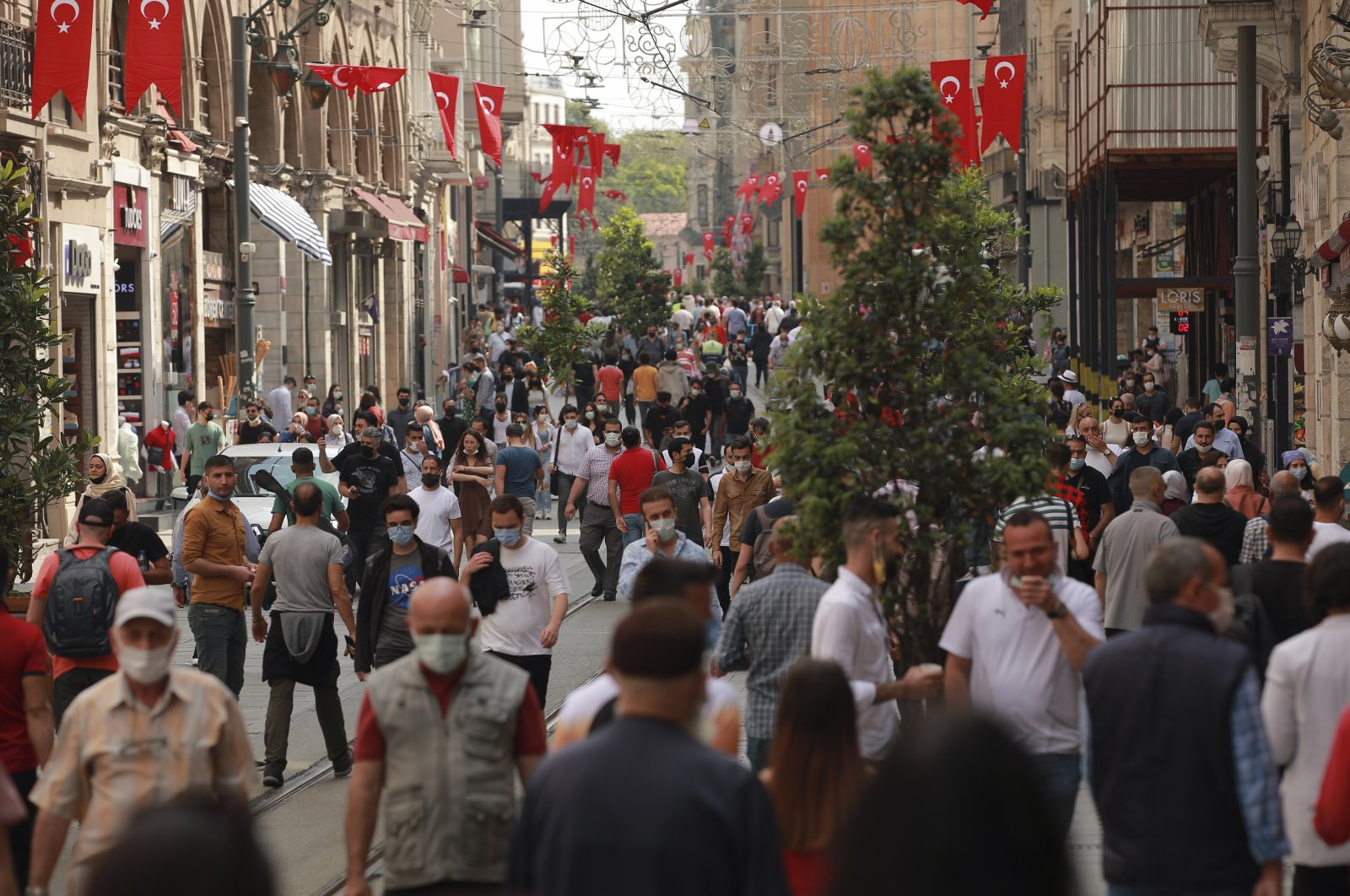 People walk on Istiklal Avenue, the main shopping street of Istanbul, Turkey, May 28, 2021. (AP Photo)