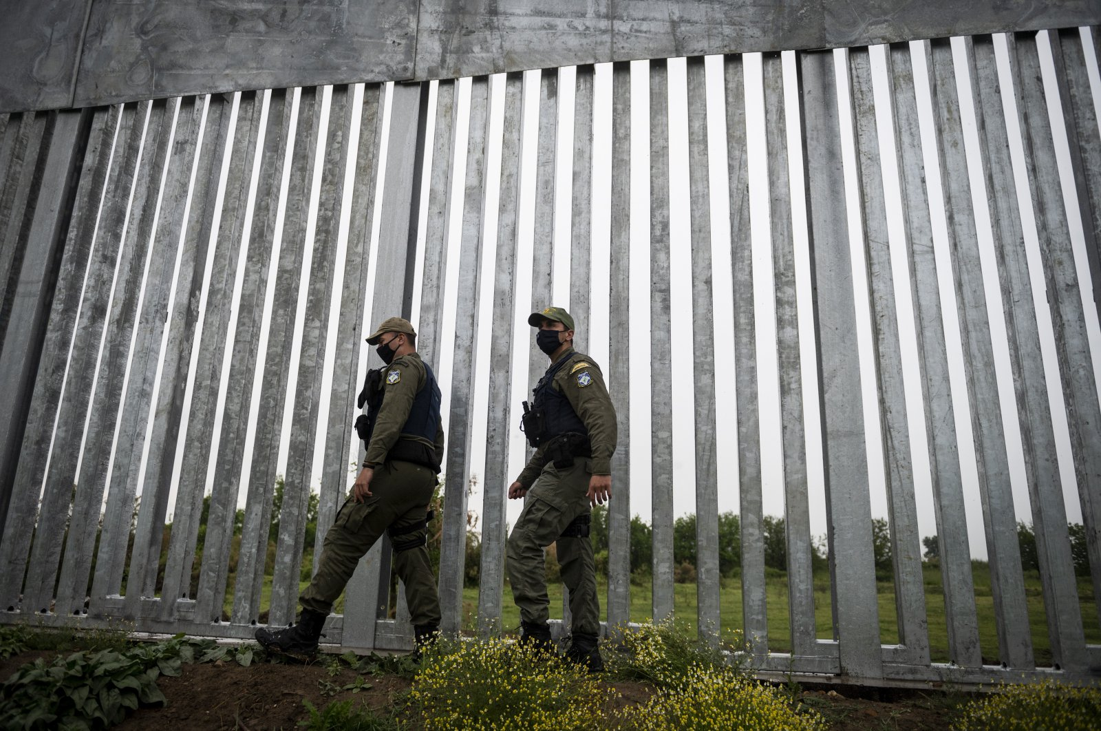 Police officers patrol alongside a steel wall at Evros river, near the village of Poros, at the Greek -Turkish border, Greece, Friday, May 21, 2021. (AP Photo)