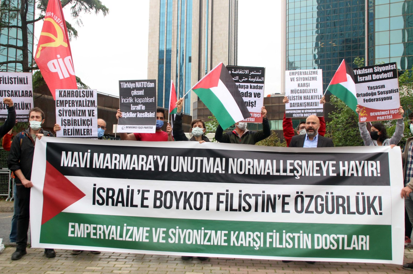 Protesters hold banners urging boycott of the Israeli government for oppressing Palestinians on the 11th anniversary of Mavi Marmara incident in front of the Israeli Consulate in Istanbul, Turkey, May 31, 2021. (DHA Photo)