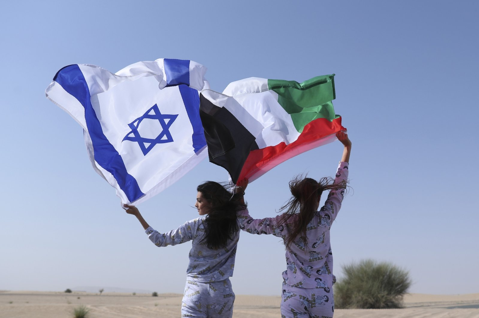 Israeli model May Tager (L) holds Israel's blue-and-white flag bearing the Star of David while next to her Anastasia Bandarenka, a Dubai-based model originally from Russia, waves the Emirati flag, during a photoshoot of Israeli fashion brand Fix, in Dubai, United Arab Emirates, Sept. 8, 2020. (AP Photo)