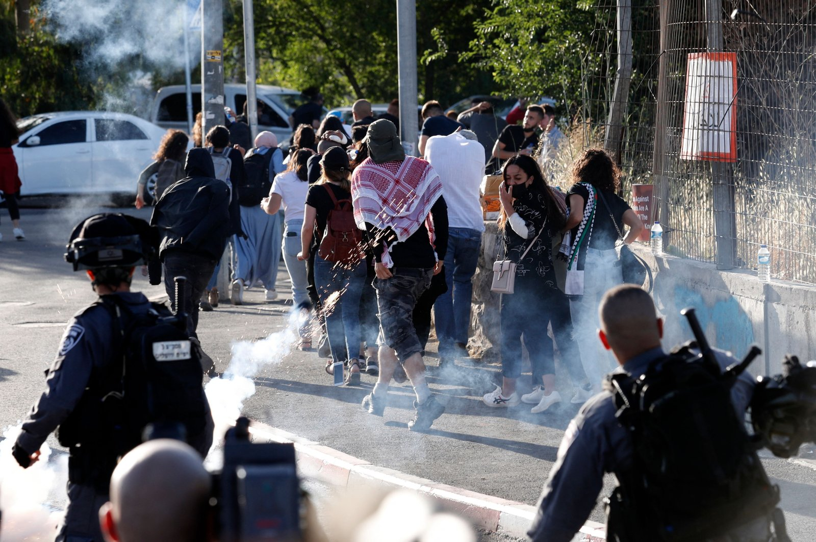 Israeli security forces fire tear gas as Palestinian protesters and activists flee, near an Israeli Police checkpoint at the entrance of the Sheikh Jarrah neighborhood in East Jerusalem, during a rally demanding the reopening of the roadblock, on May 29, 2021. (AFP Photo)