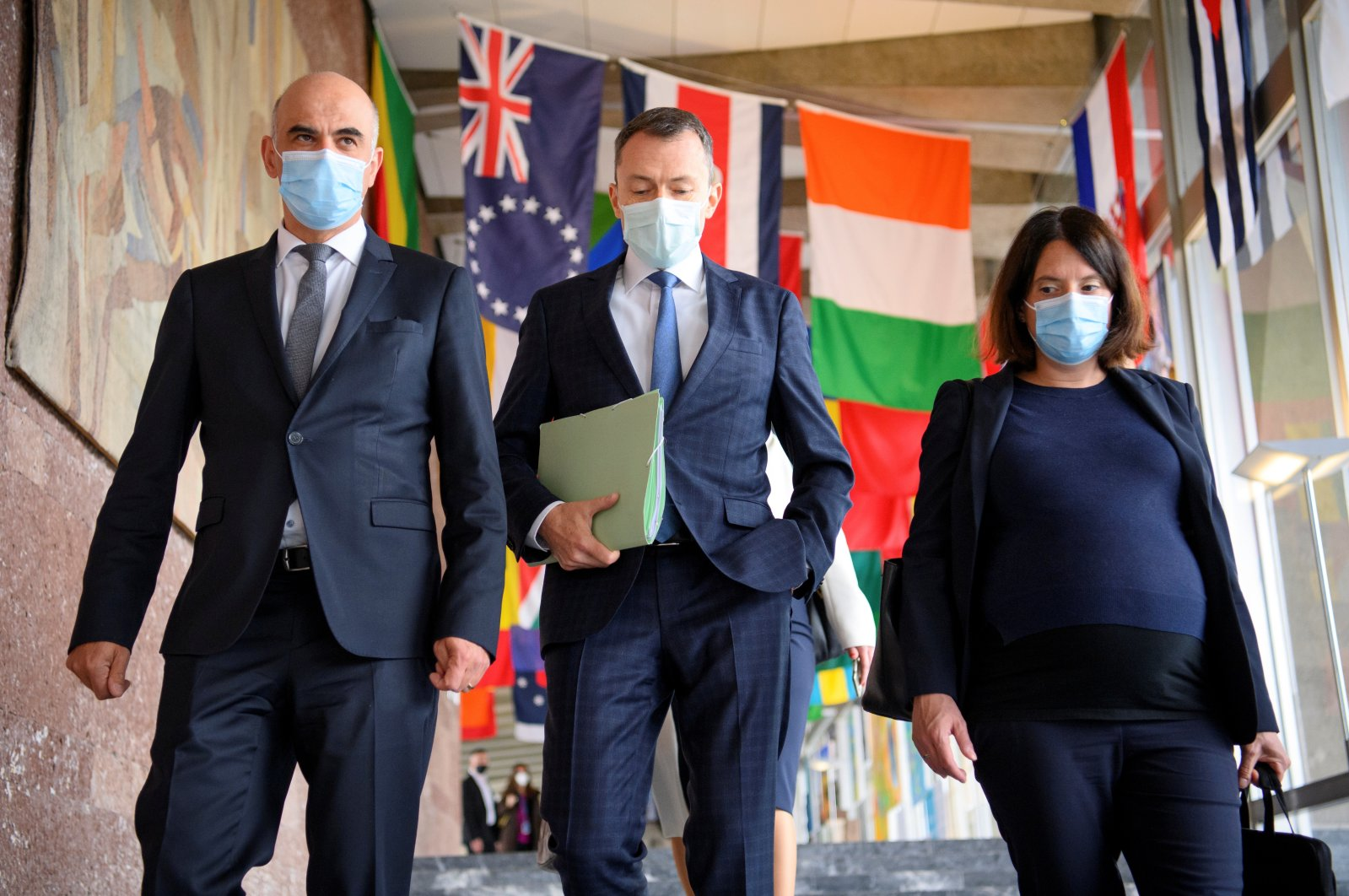 (L-R) Swiss Interior and Health Minister Alain Berset walks with the Swiss ambassador and permanent representative of Switzerland to the United Nations, Juerg Lauber, and Swiss Ambassador Nora Kronig Romero, the head of the International Affairs Division and vice director of the Federal Office of Public Health, before speaking at the opening of the 74th World Health Assembly at the World Health Organization headquarters, in Geneva, Switzerland, May 24, 2021. (Laurent Gillieron/Pool via Reuters)