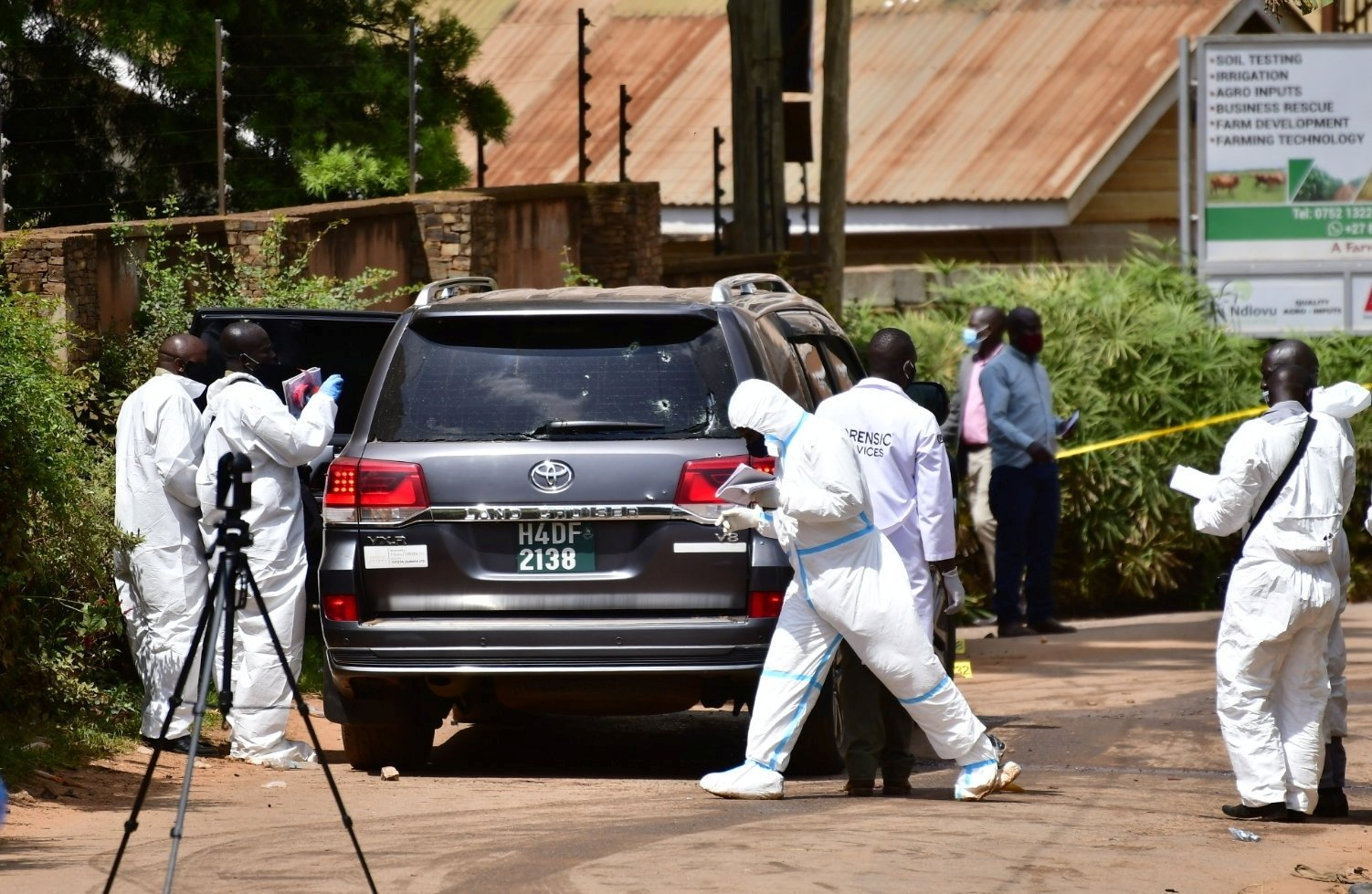 Forensic experts secure the scene of an attempted assassination on Ugandan minister of works and transport General Katumba Wamala, in which he was wounded and his daughter and driver killed, near Kampala, Uganda June 1, 2021. (Reuters Photo)