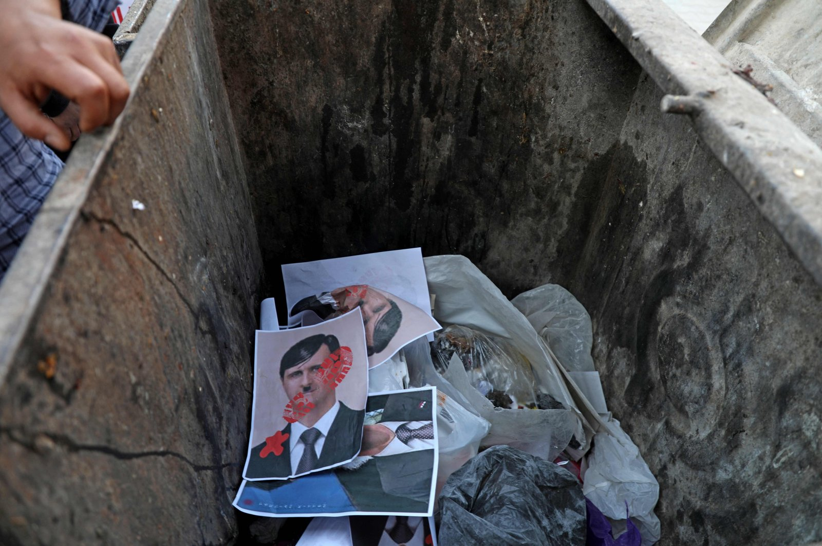 Syrians throw posters depicting Bashar Assad as Adolf Hitler in a garbage bin symbolizing a ballot box in the town of Dana, east of the Turkish-Syrian border in Idlib province, northwestern Syria, May 24, 2021. (AFP Photo)