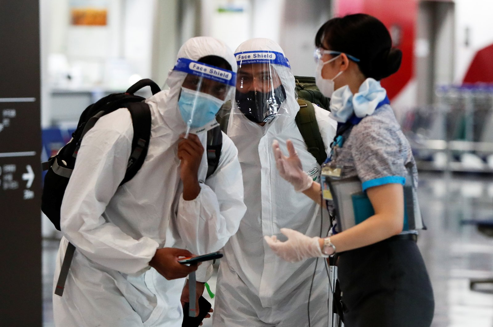Passengers wearing personal protection equipment (PPE) are escorted by an airline employee at Narita international airport, amid the coronavirus pandemic, Narita, Tokyo, Japan, June 1, 2021.  (Reuters Photo)