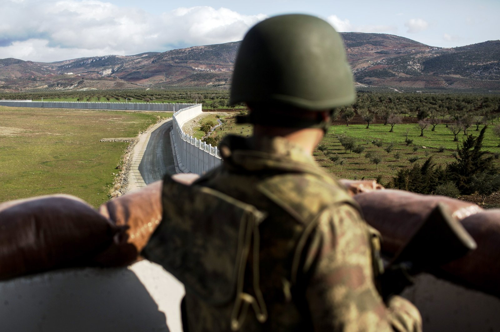 A Turkish soldier from the 1st Border Regiment Command looks out over the border wall to Syria during alert drills at a military outpost on the Turkey-Syria border, Kilis, Turkey, March 2, 2017. (Getty Images)