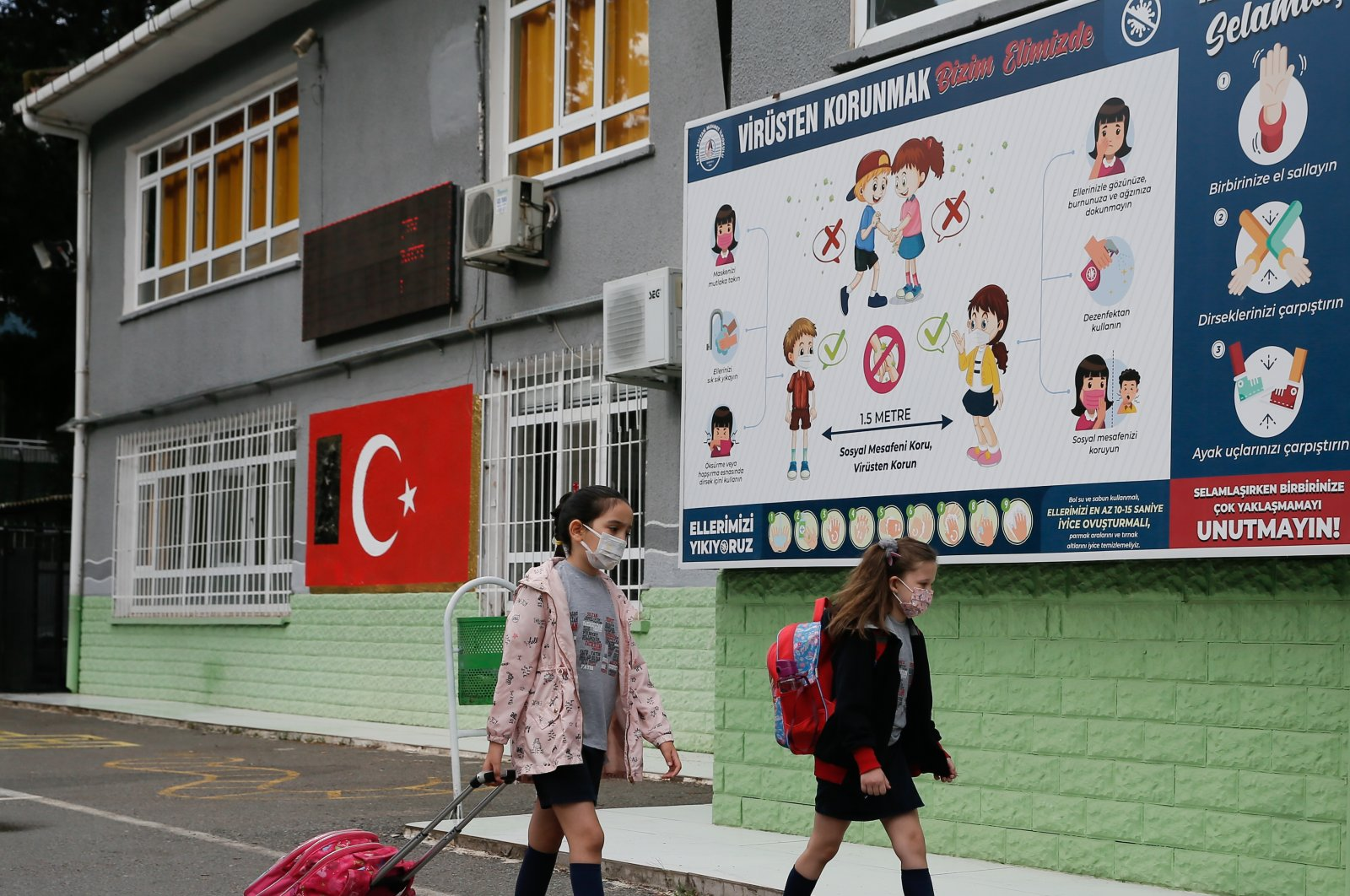 Children walk past a billboard about COVID-19 en route to school, in Izmir, western Turkey, June 1, 2021. (AA PHOTO)
