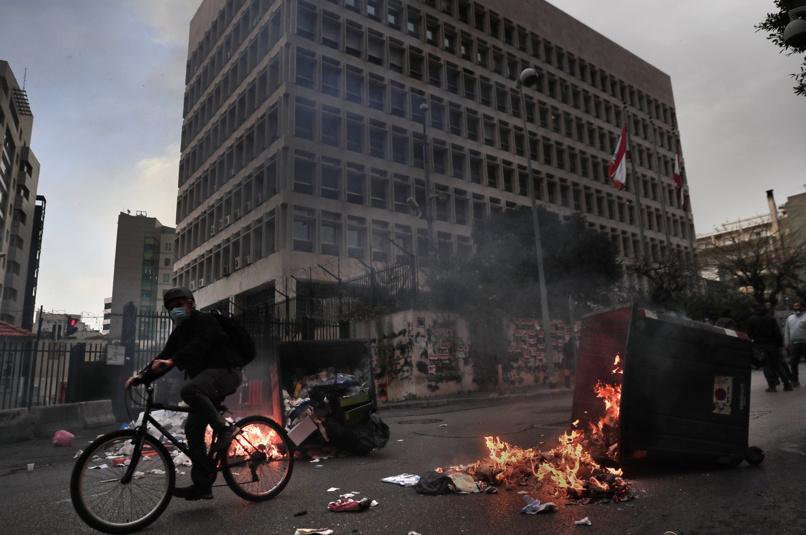 A man rides his bicycle past garbage containers set on fire by protesters blocking a main road in front of the Lebanese Central Bank building, Beirut, Lebanon, March 22, 2021. (AP Photo)