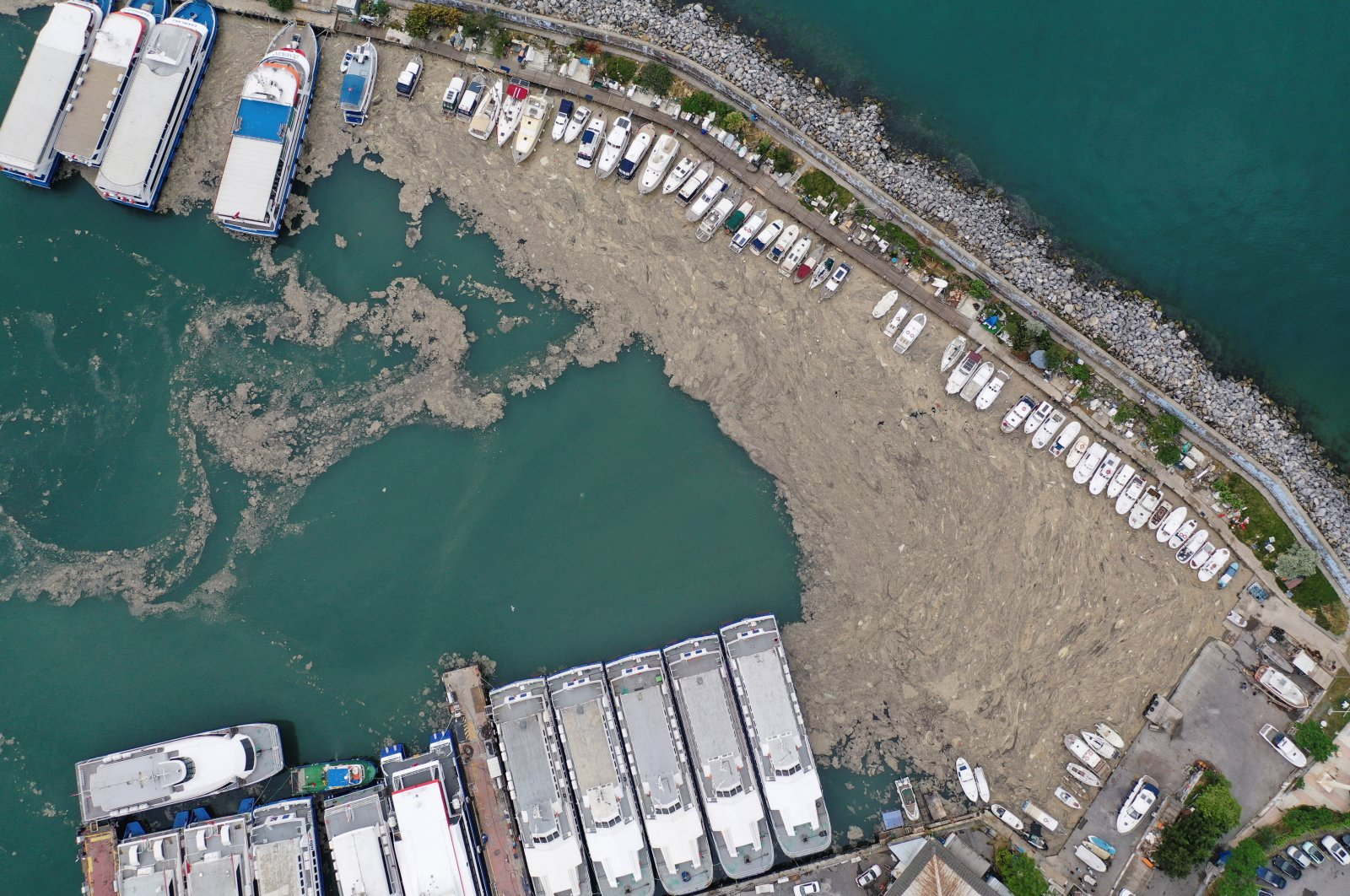 """An aerial view shows a thick layer of """"sea snot,"""" consisting of a wide variety of microorganisms, that covers the sea near the coast in the Bostancı harbor in Istanbul, Turkey, May 31, 2021. (Reuters Photo)"""