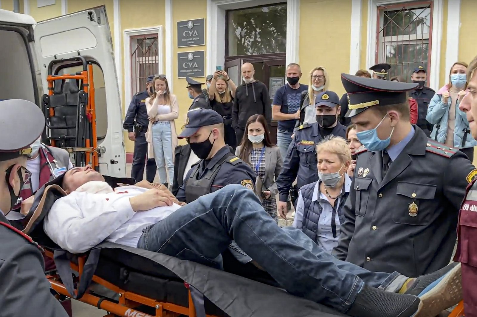 Police officers and paramedics carry Stsiapan Latypau, a Belarusian activist who attempted to kill himself during a court hearing to protest political repression, into an ambulance in Minsk, Belarus, June 1, 2021. (Radio Free Europe/Radio Liberty via AP)