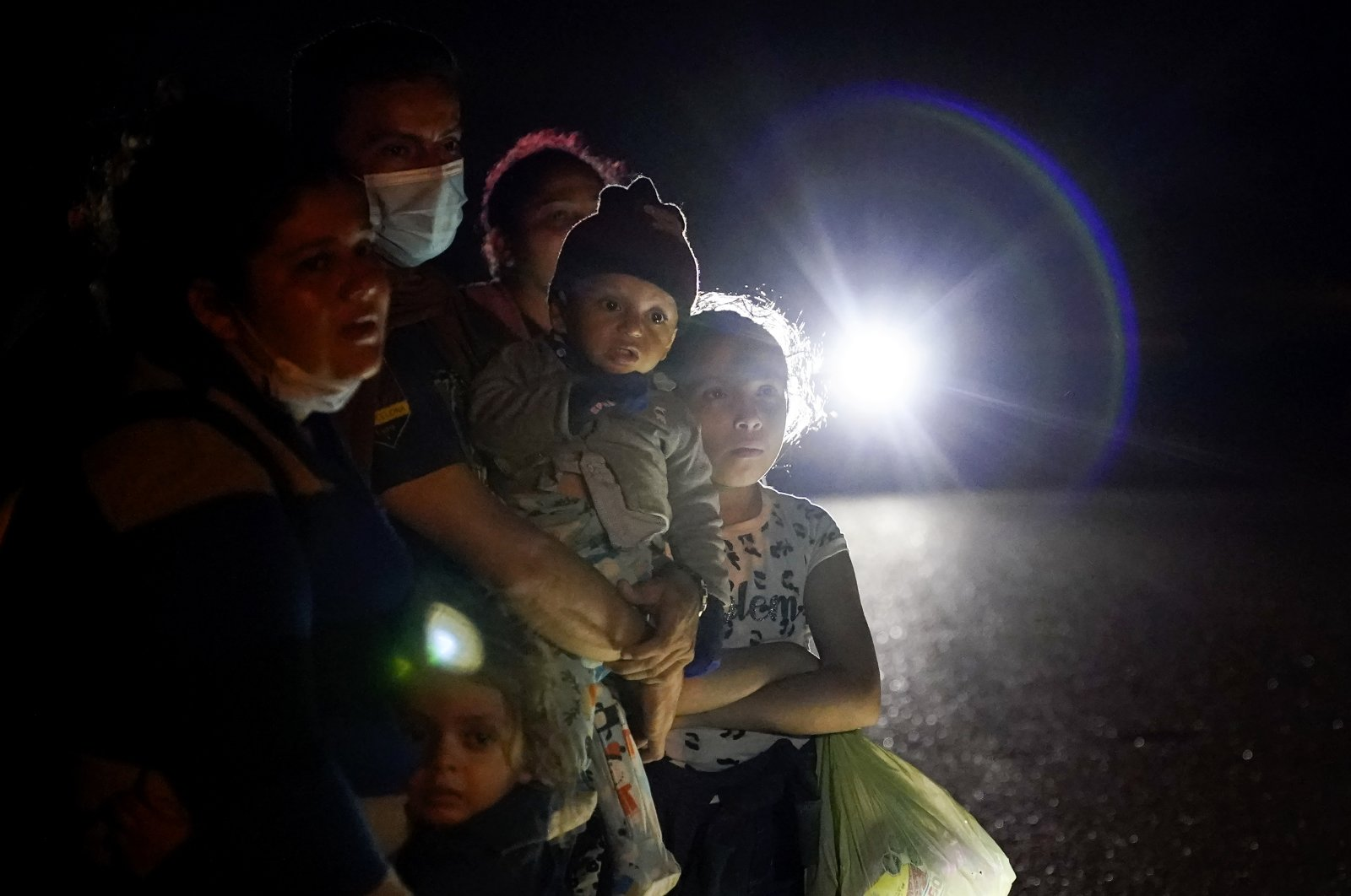 A group of migrants mainly from Honduras and Nicaragua wait along a road after turning themselves in upon crossing the U.S.-Mexico border, in La Joya, Texas, U.S., May 17, 2021. (AP Photo)