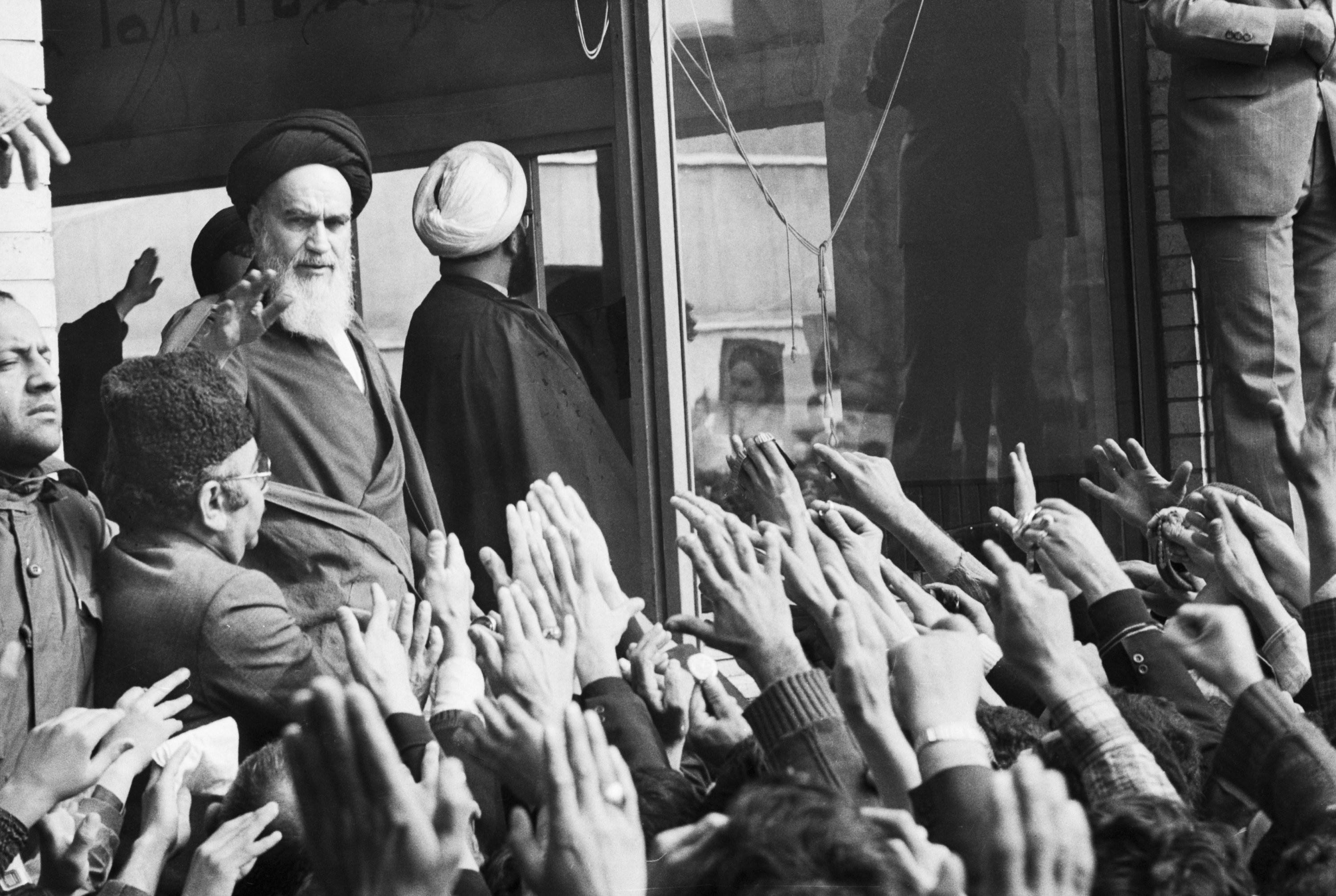 Ayatollah Khomeini waves to a crowd of supporters from the window of his Tehran home, Iran, Feb. 7, 1979. (Photo by Getty Images)