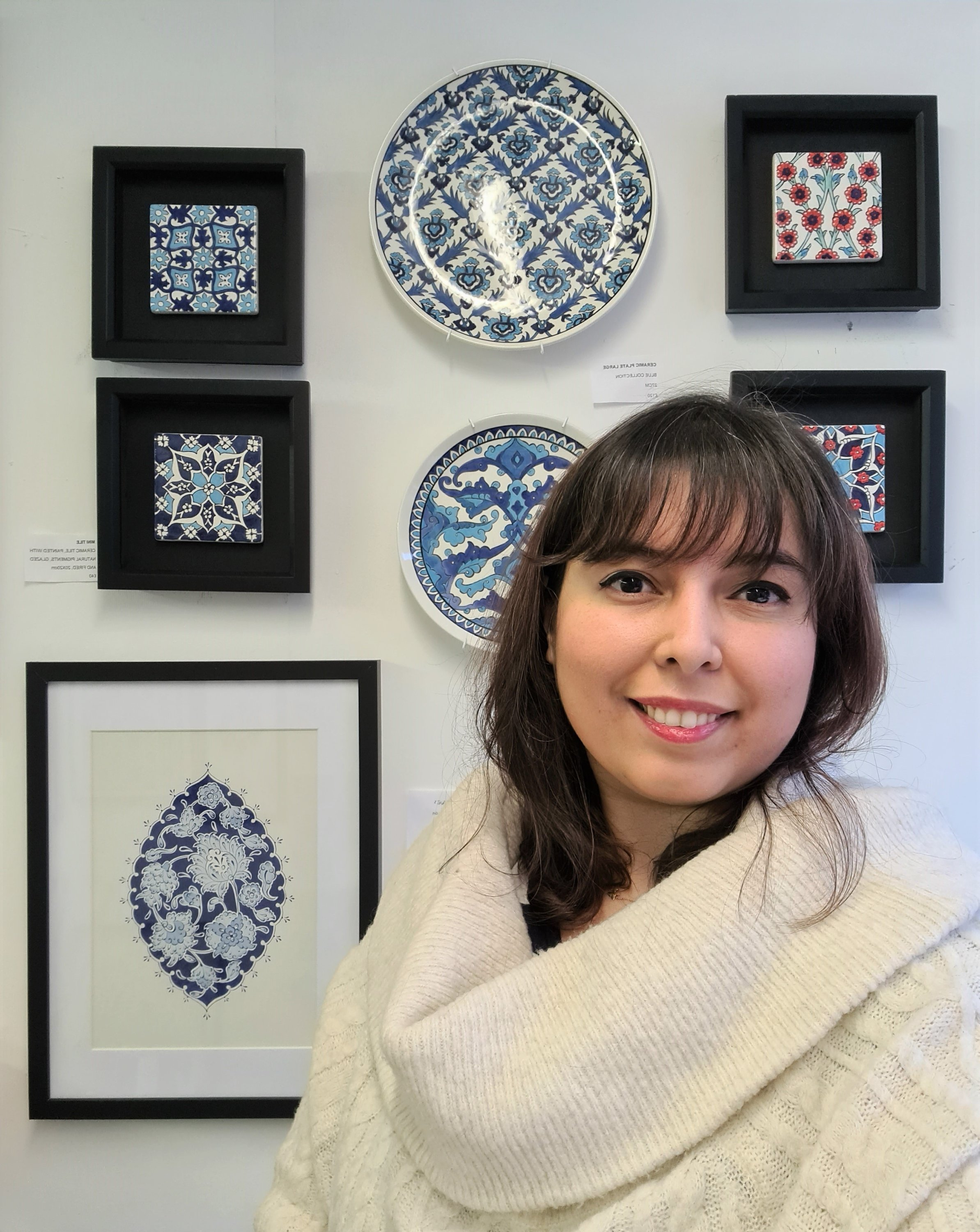 """Nagihan Seymour poses in front of some works from """"The Four Elements.' (Courtesy of Nagihan Seymour)"""