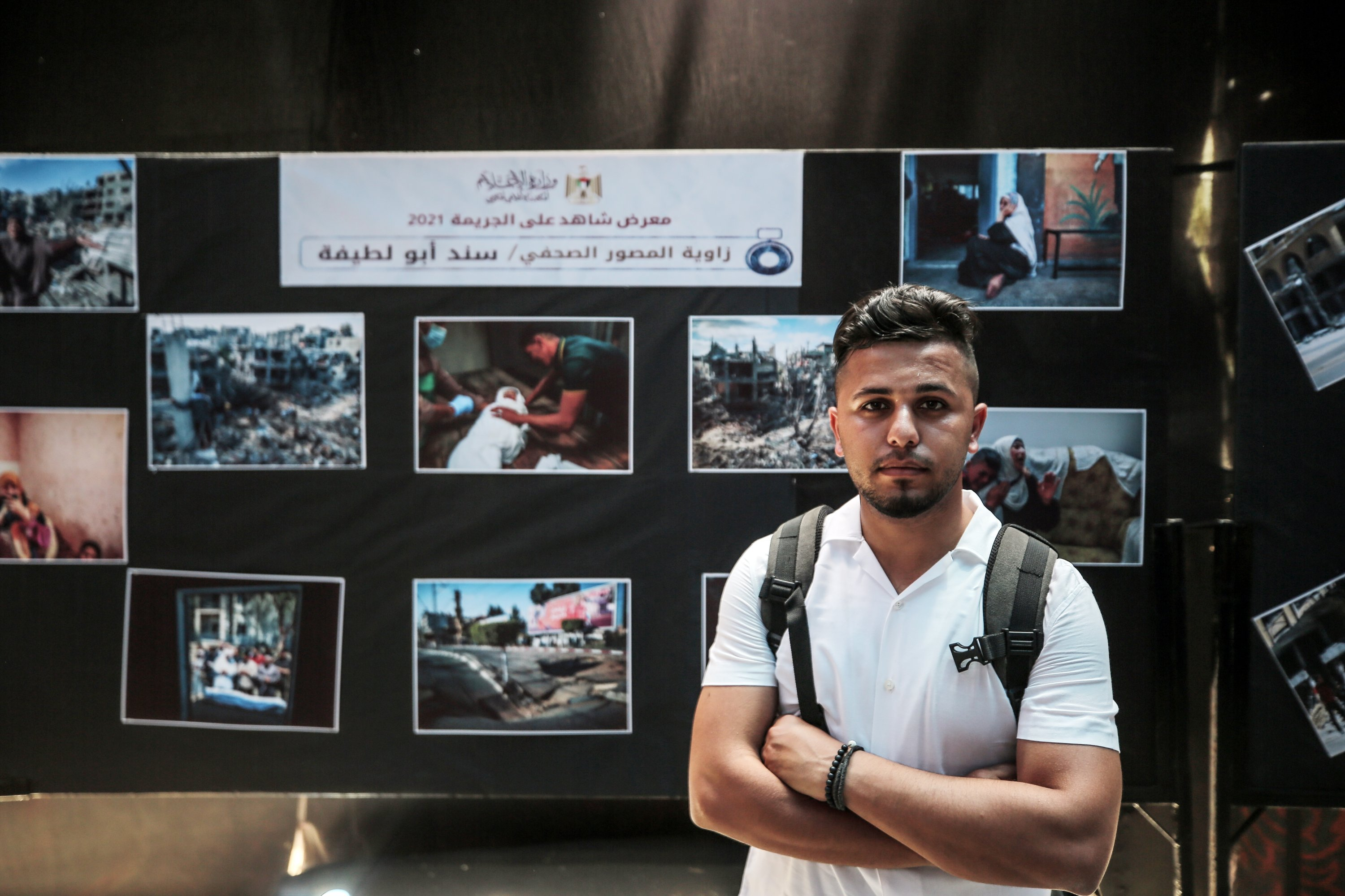 A photojournalist poses in front of some photos at the 'Witness to the 2021 Crime' exhibition in the Gaza Strip, Palestine, June 1, 2021. (AA Photo)