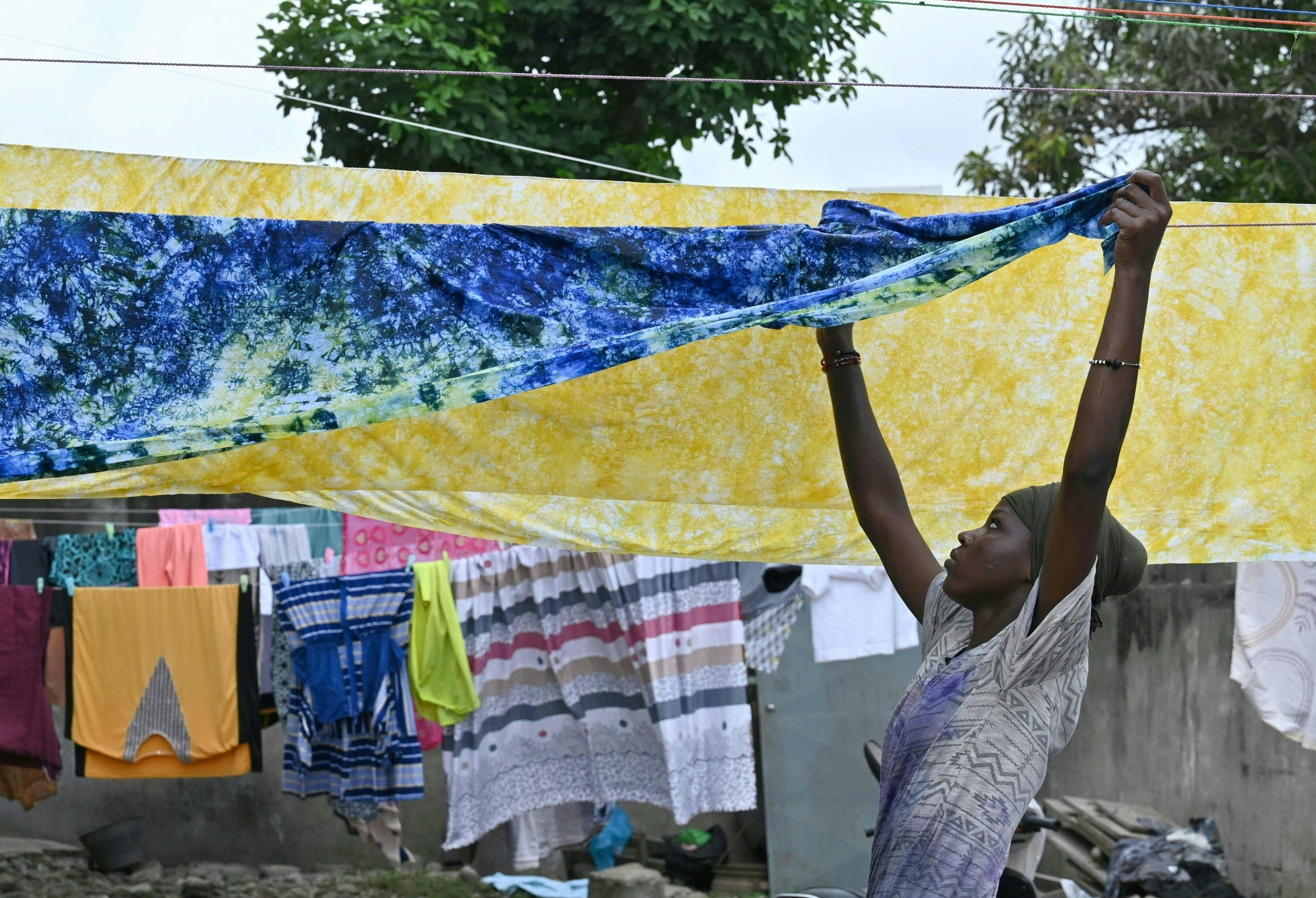 A woman hangs up dyed cotton fabric to dry at Pathe'O house in the popular district of Treichville in Abidjan, Ivory Coast, March 31, 2021. (AFP Photo)