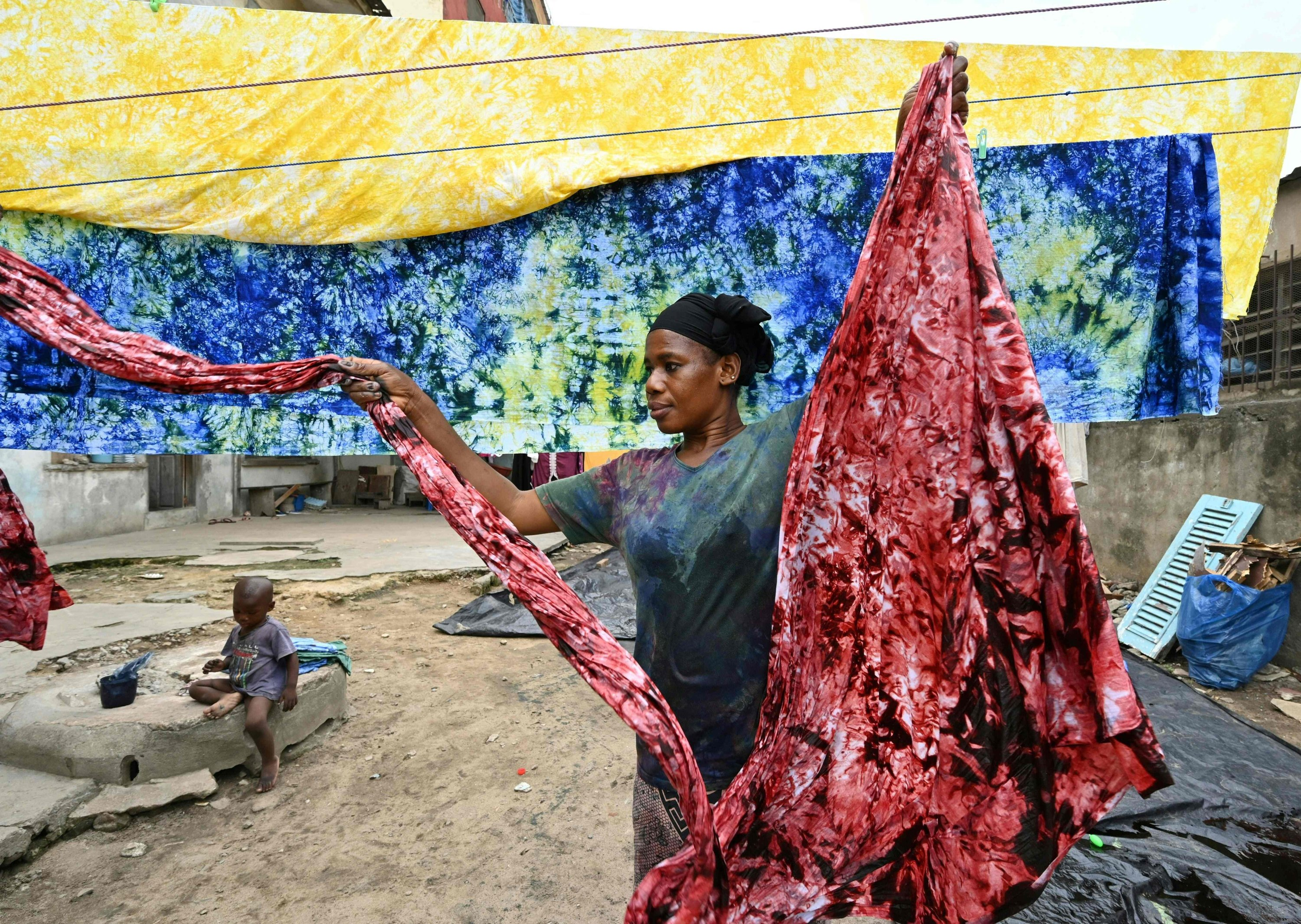Dyers dye cotton fabric at Pathe'O house in the popular district of Treichville in Abidjan, Ivory Coast, March 31, 2021. (AFP Photo)