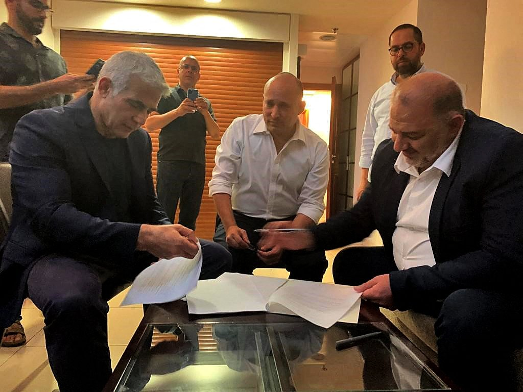 The head of the Arab Israeli conservative party Raam's Mansour Abbas (R) signing a coalition agreement with Israel's opposition leader Yair Lapid (L) and right-wing nationalist tech millionaire Naftali Bennett in Ramat Gan near the coastal city of Tel Aviv, Israel, June 2, 2021. (AFP Photo via United Arab List Raam)