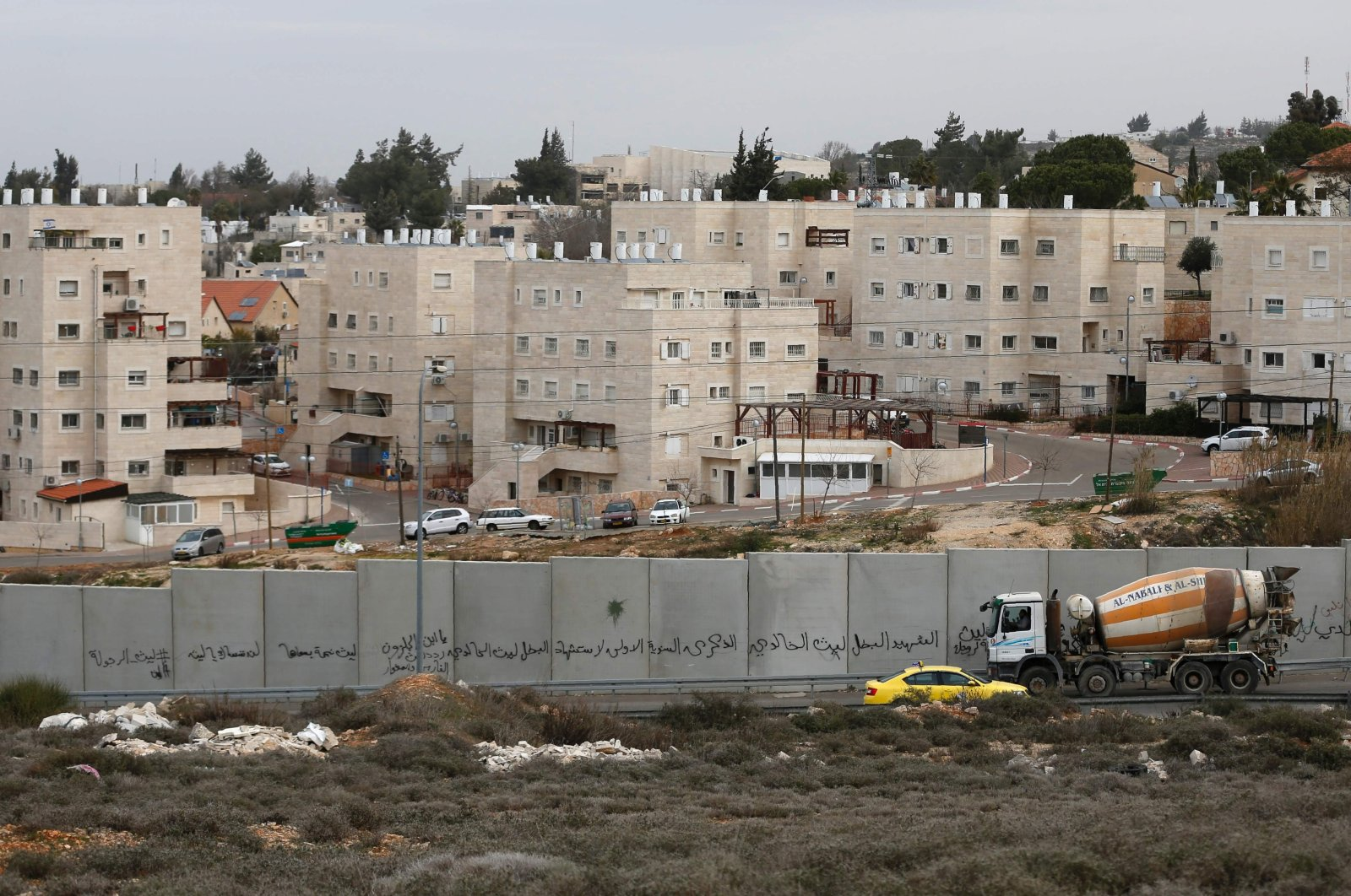 A photograph of Israel's controversial separation barrier and the settlement of Beit El behind it, taken from the city of Ramallah, West Bank, Palestine, Jan. 25, 2017. (AFP File Photo)