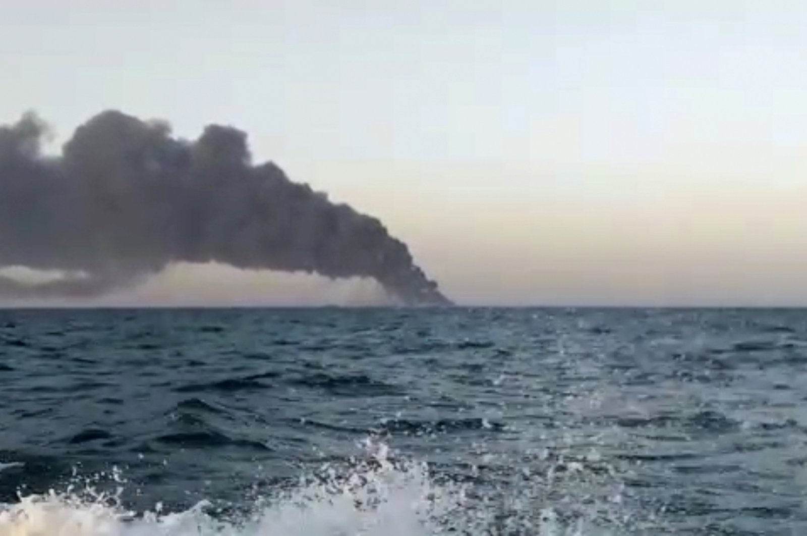 This image made from a video released on Wednesday, June 2, 2021 by Asriran.com, shows smoke rising from Iran's navy support ship Kharg in the Gulf of Oman. (AP Photo)