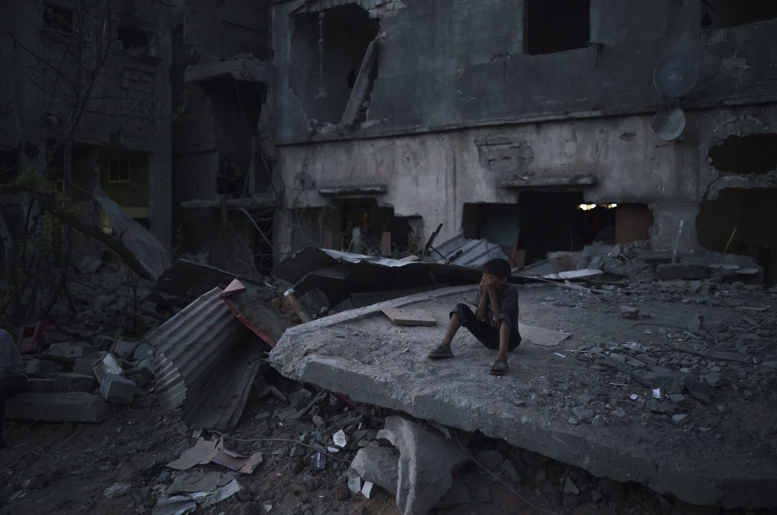 A boy sits on a destroyed building in a neighborhood heavily damaged by Israeli airstrikes, in Beit Hanoun, Gaza Strip, Palestine, May 31, 2021. (AP Photo)