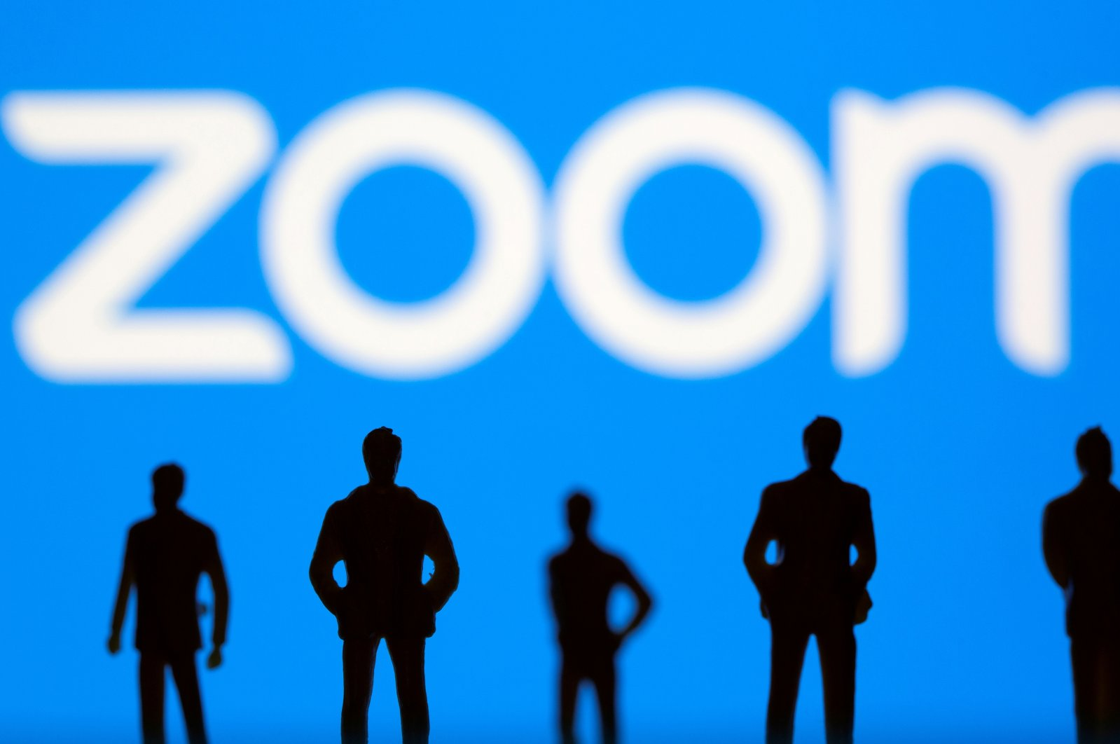 Small toy figures are seen in front of the Zoom logo in this illustration picture taken March 15, 2021. (Reuters Photo)