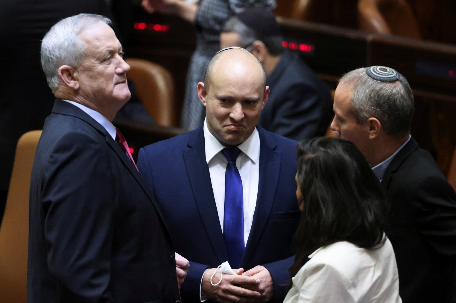 Defense Minister and leader of Blue and White party Benny Gantz (L) speaks to Yamina leader Naftali Bennett (C) during a special session of the Knesset, Jerusalem, Israel, June 2, 2021. (Reuters Photo)
