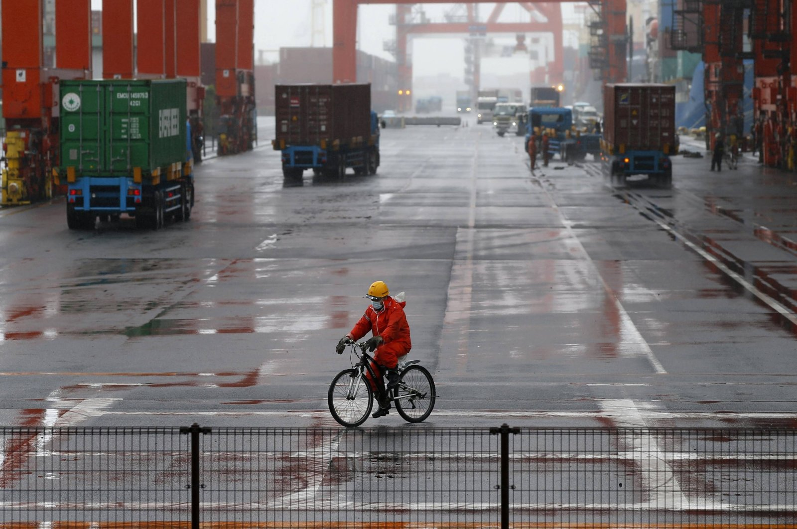 A worker rides a bicycle in a container area at a port in Tokyo, Japan, May 21, 2014. (Reuters Photo)