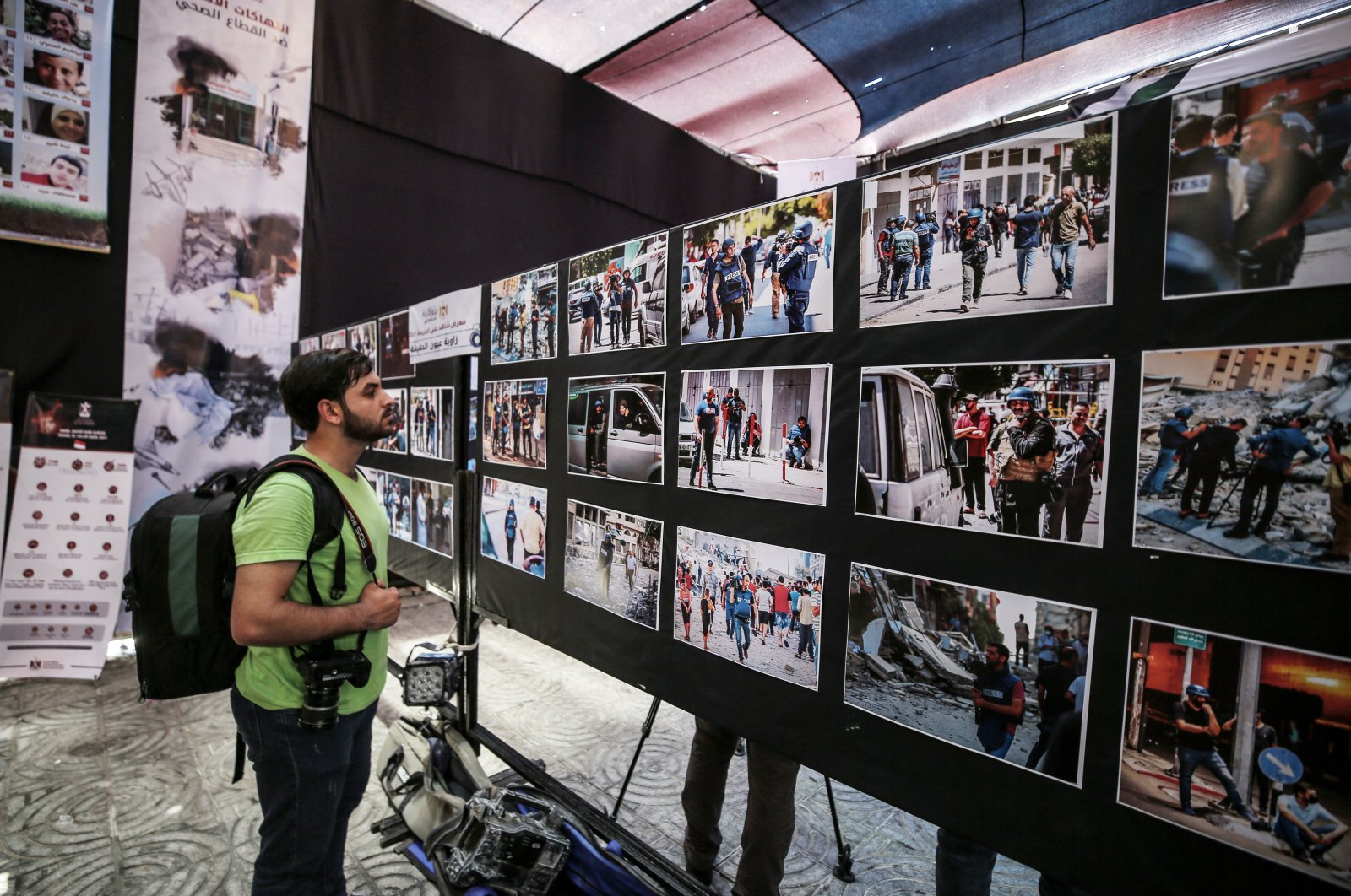 """A visitor examines photos at the """"Witness to the 2021 Crime"""" exhibition in the Gaza Strip, Palestine, June 1, 2021. (AA Photo)"""