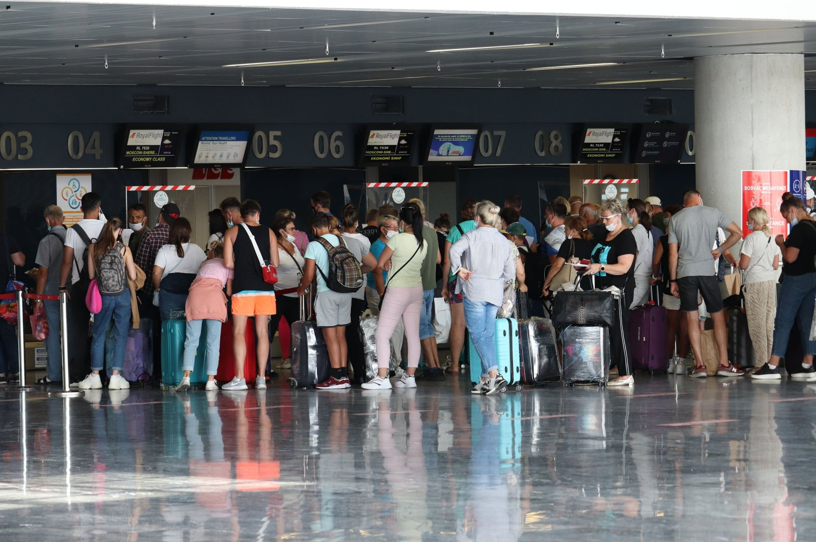 Tourists in masks standing with luggage wait in line at the Milas-Bodrum Airport, Bodrum, southwestern Turkey, Sept. 28, 2020. (Shutterstock Photo)