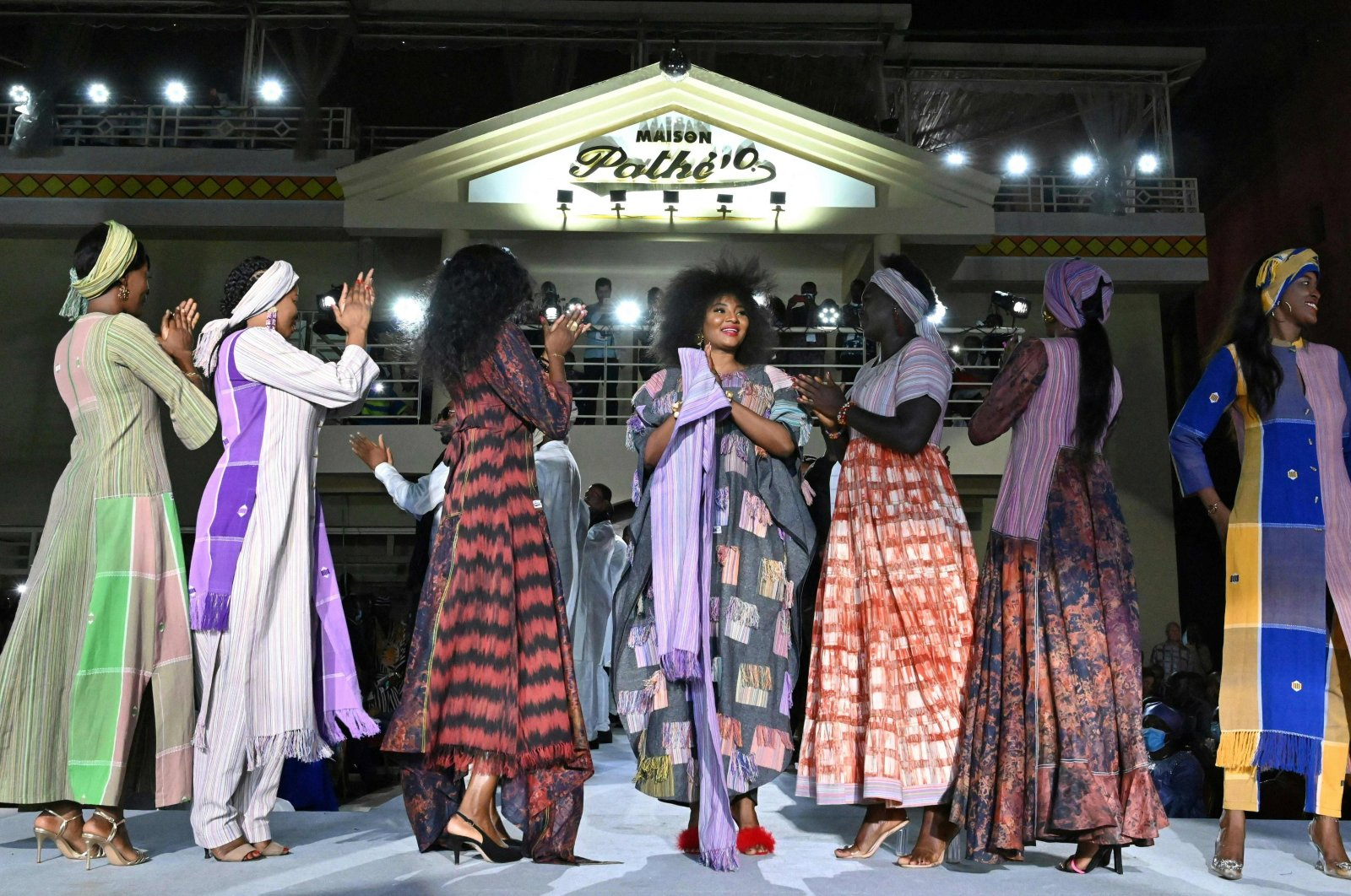 """Models present Pathe'O's curations during a fashion show celebrating 50 years of """"Maison Pathe'O"""" in Abidjan, Ivory Coast, May 29, 2021. (AFP Photo)"""