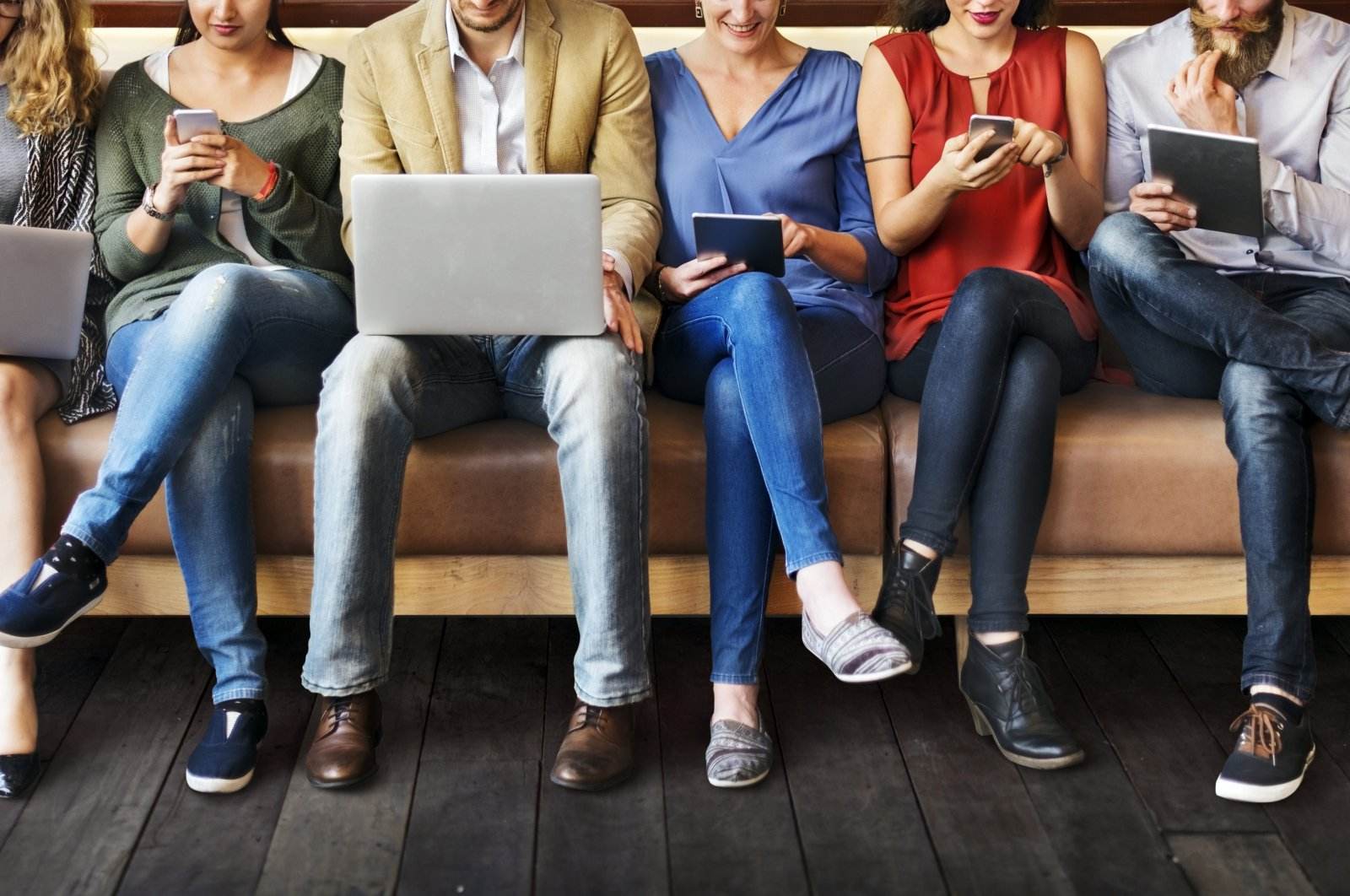 A group of people busy with their laptops, tablets and phones. (iStockphoto Photo)