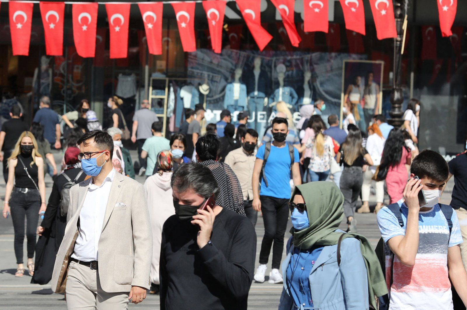 People wearing face masks walk along a street, in the capital Ankara, Turkey, May 21, 21021. (AFP Photo)