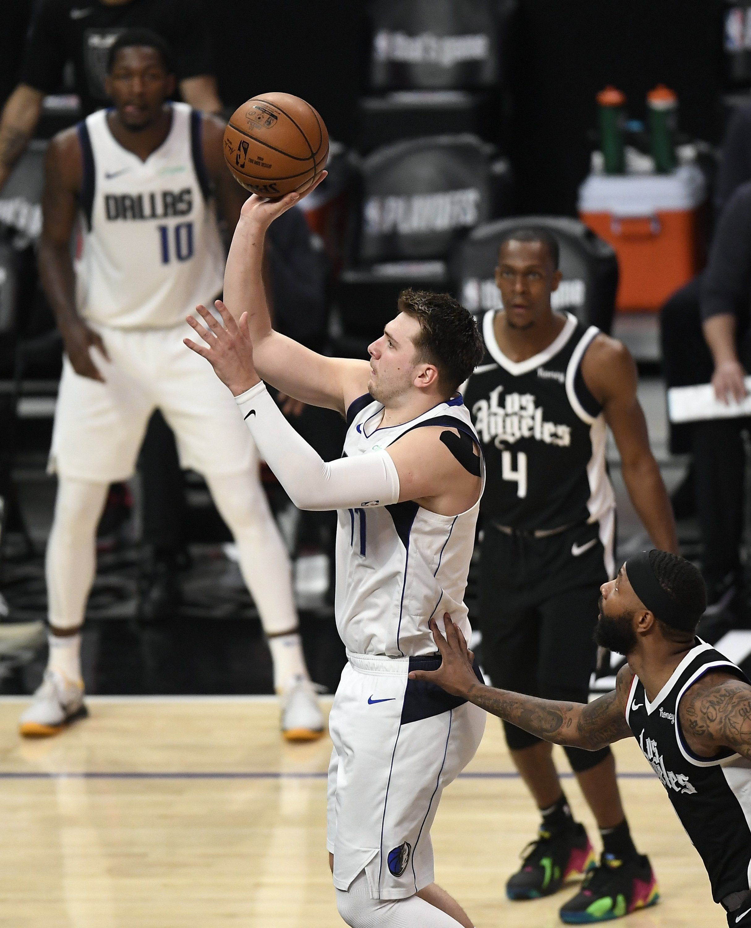 Dallas Mavericks' Luka Doncic (L) scores against the Los Angeles Clippers during game five of a Western Conference first-round NBA Playoffs at Staples Center, Los Angeles, California, U.S., June 2, 2021.