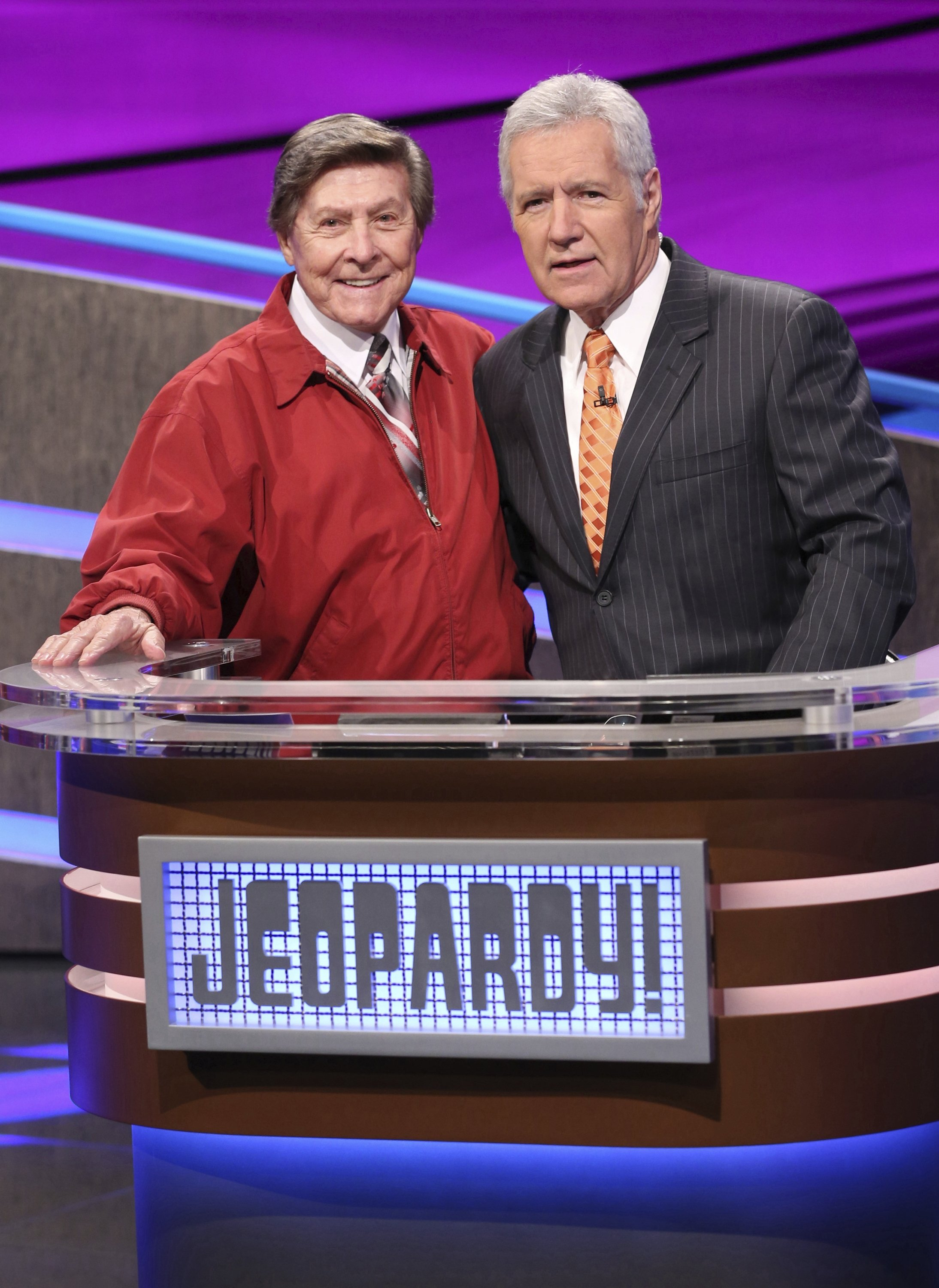 In this 2014 image provided by Jeopardy Productions, Inc., show announcer Johnny Gilbert (L) and game show host Alex Trebek appear on the set of 'Jeopardy!'  (Carol Kaelson/Jeopardy Productions, Inc. via AP)